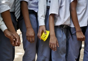 A student holds his tiffin box while standing in a queue to receive free mid-day meal being distributed by municipal workers at a government school in New Delhi, India, May 6, 2015.