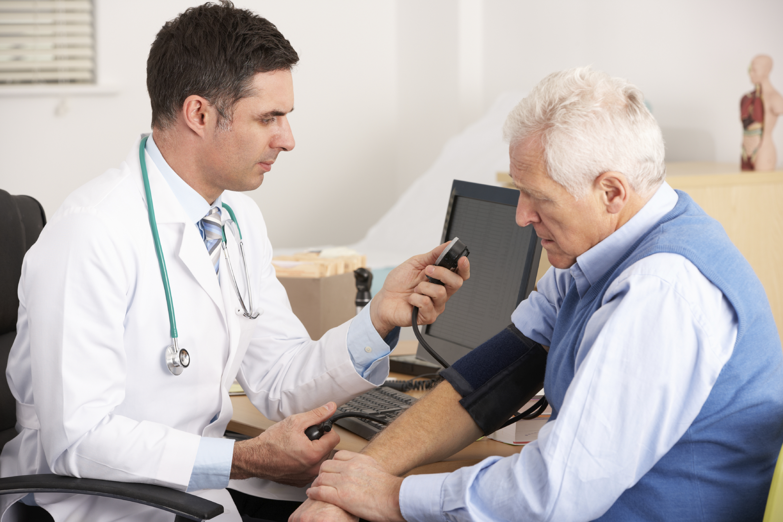 An elderly man gets his blood pressure taken