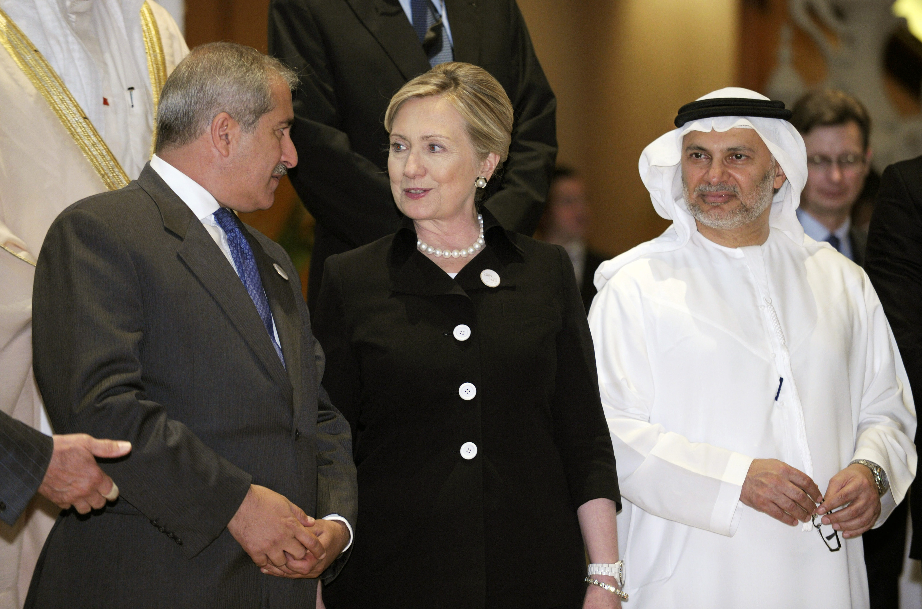 U.S. Secretary of State Hillary Rodham Clinton (C) speaks with Jordan's Foreign Minister Nasser Judeh (L) and United Arab Emirates Minister of State for Foreign Affairs Anwar Gargash as they participate in the Libya Contact Group family photo at the Emirates Palace Hotel in Abu Dhabi