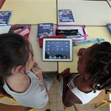 Elementary school children share an electronic tablet on the first day of class in the new school year in Nice, September 3, 2013.