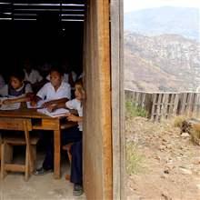 Honduran children attend a class at an outdoors makeshift school at a shantytown on the outskirts of Tegucigalpa.