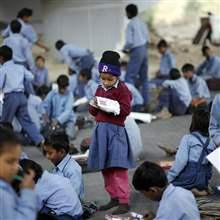 A schoolgirl reads from a textbook at an open-air school in New Delhi November 20, 2014.