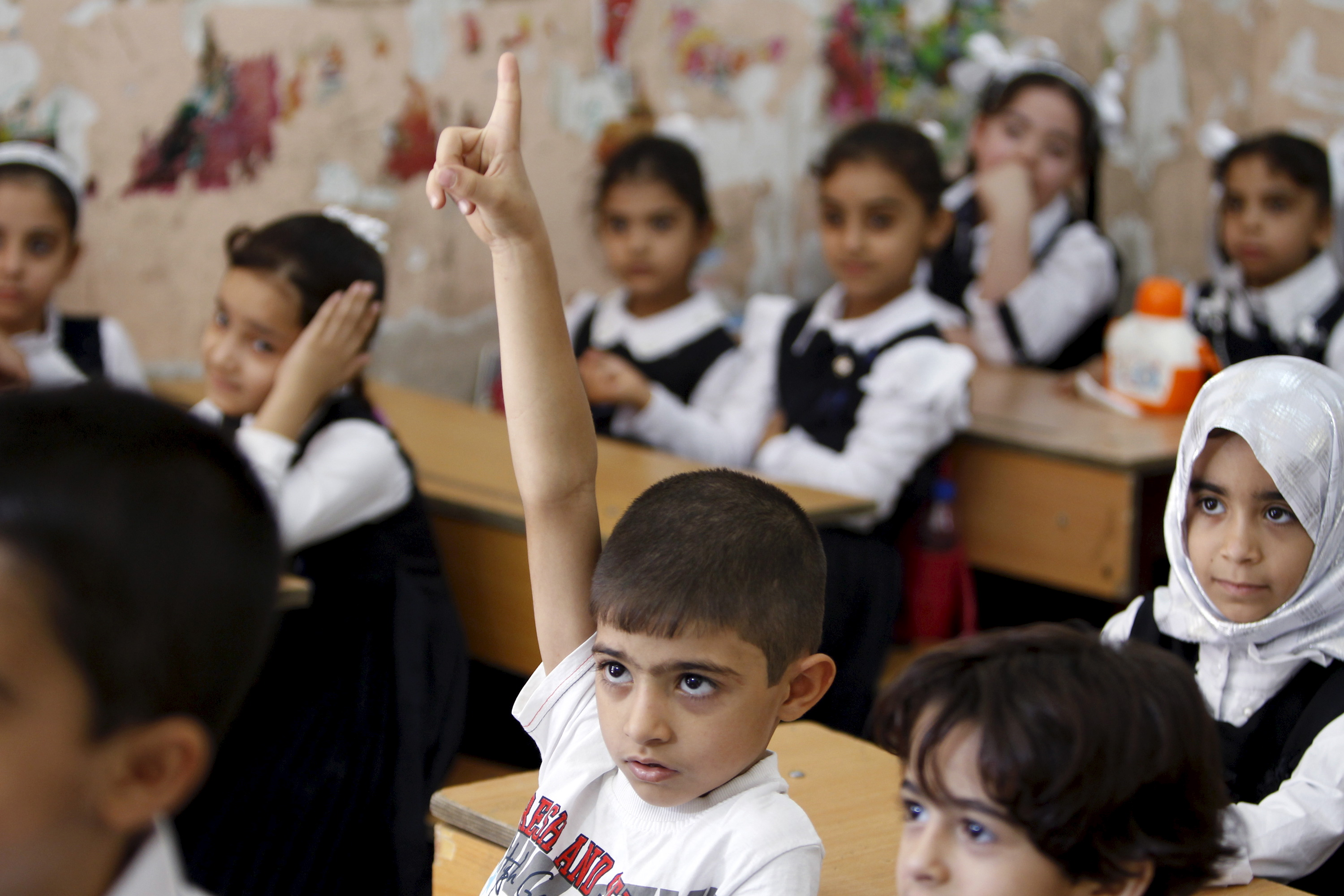 A student raises his hand while attending the first day of the new school term at a primary school in Baghdad, October 18, 2015.