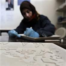 A Jordanian employee engraves a handcrafted ceramic salver at a Beit al Bawadi ceramics workshop in Amman January 7, 2014.