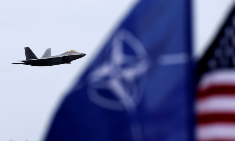 NATO and U.S. flags flutter as U.S. Air Force F-22 Raptor fighter flies over the military air base in Siauliai, Lithuania, April 27, 2016. REUTERS/Ints Kalnins