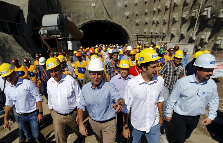 Rio de Janeiro's Mayor Eduardo Paes (C) and Rio de Janeiro's Governor Luiz Fernando Pezao (2nd L) leave one of the two tunnels on the Transolimpica freeway route, which will connect the Rio 2016 Olympic Park and the Deodoro Sports Complex, in Rio de Janeiro, Brazil August 4, 2015. The transportation project is being carried out for the city's redevelopment ahead of the 2016 Olympic Games. REUTERS/Ricardo Moraes - RTX1N13J