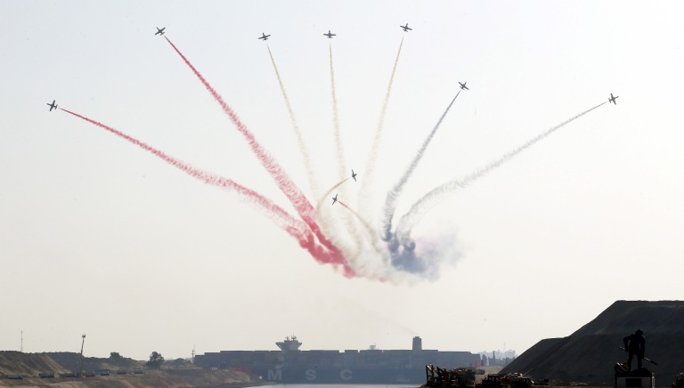 Egyptian air force planes parade in front of a cargo container ship crossing the new section of the Suez Canal after the opening ceremony of the new Suez Canal, in Ismailia, Egypt, August 6, 2015. Egypt staged a show of international support on Thursday as it inaugurated a major extension of the Suez Canal which President Abdel Fattah al-Sisi hopes will power an economic turnaround in the Arab world's most populous country. REUTERS/Amr Abdallah Dalsh REUTERS/Amr Abdallah Dalsh - RTX1NCNT