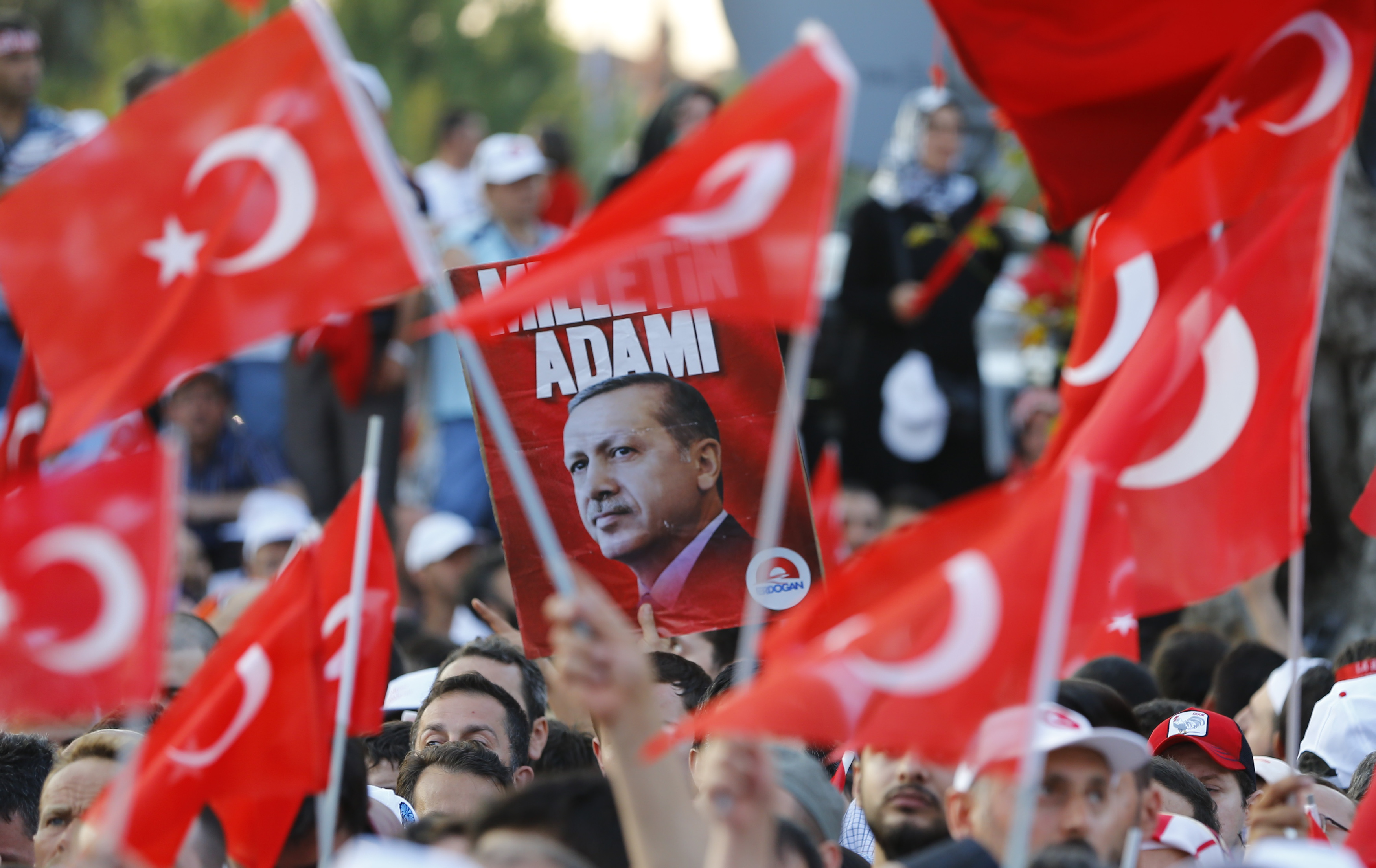 People wave flags as they wait for Turkish President Tayyip Erdogan to speak in Istanbul, Turkey.