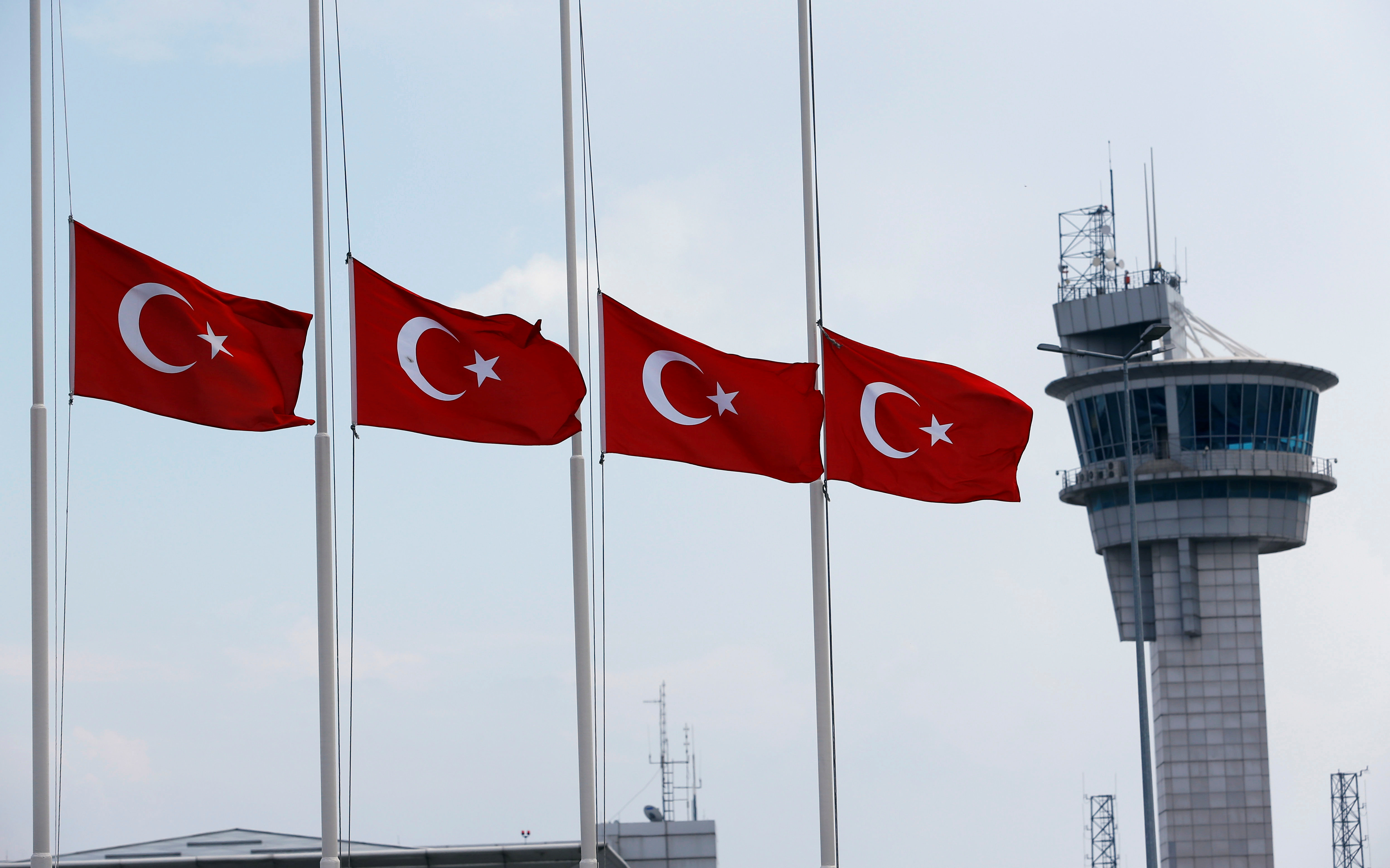 Reuters/Murad Seze - Turkish flags, with the control tower in the background, fly at half mast at the country's largest airport, Istanbul Ataturk, following yesterday's blast in Istanbul, Turkey, June 29, 2016