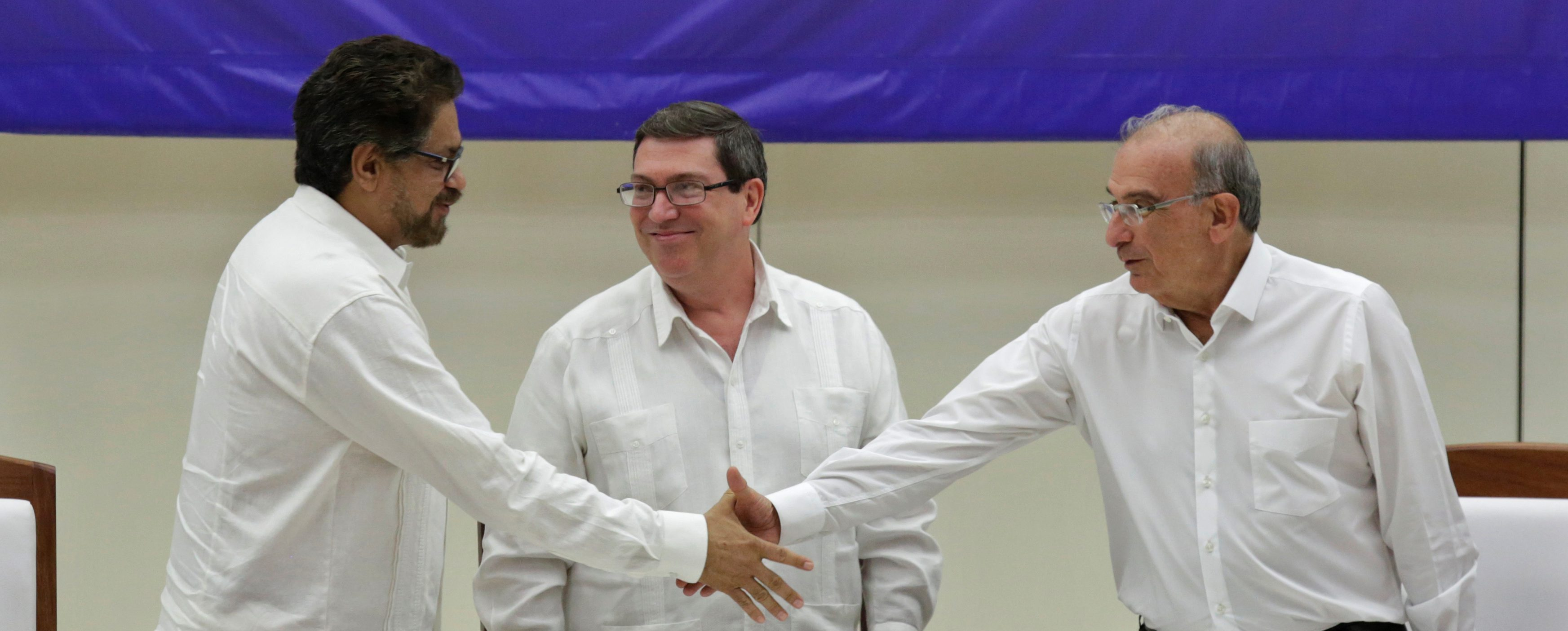 Colombia's FARC lead negotiator Ivan Marquez (L) and Colombia's lead government negotiator Humberto de la Calle (R) shake hands while Cuba's Foreign Minister Bruno Rodriguez looks on, after signing a final peace deal in Havana, Cuba, August 24, 2016. REUTERS/Enrique de la Osa - RTX2MXPE