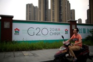A man rides an electronic bike past a billboard for the upcoming G20 summit in Hangzhou, Zhejiang province, China, July 29, 2016. Picture taken July 29, 2016. REUTERS/Aly Song - RTSL4WW