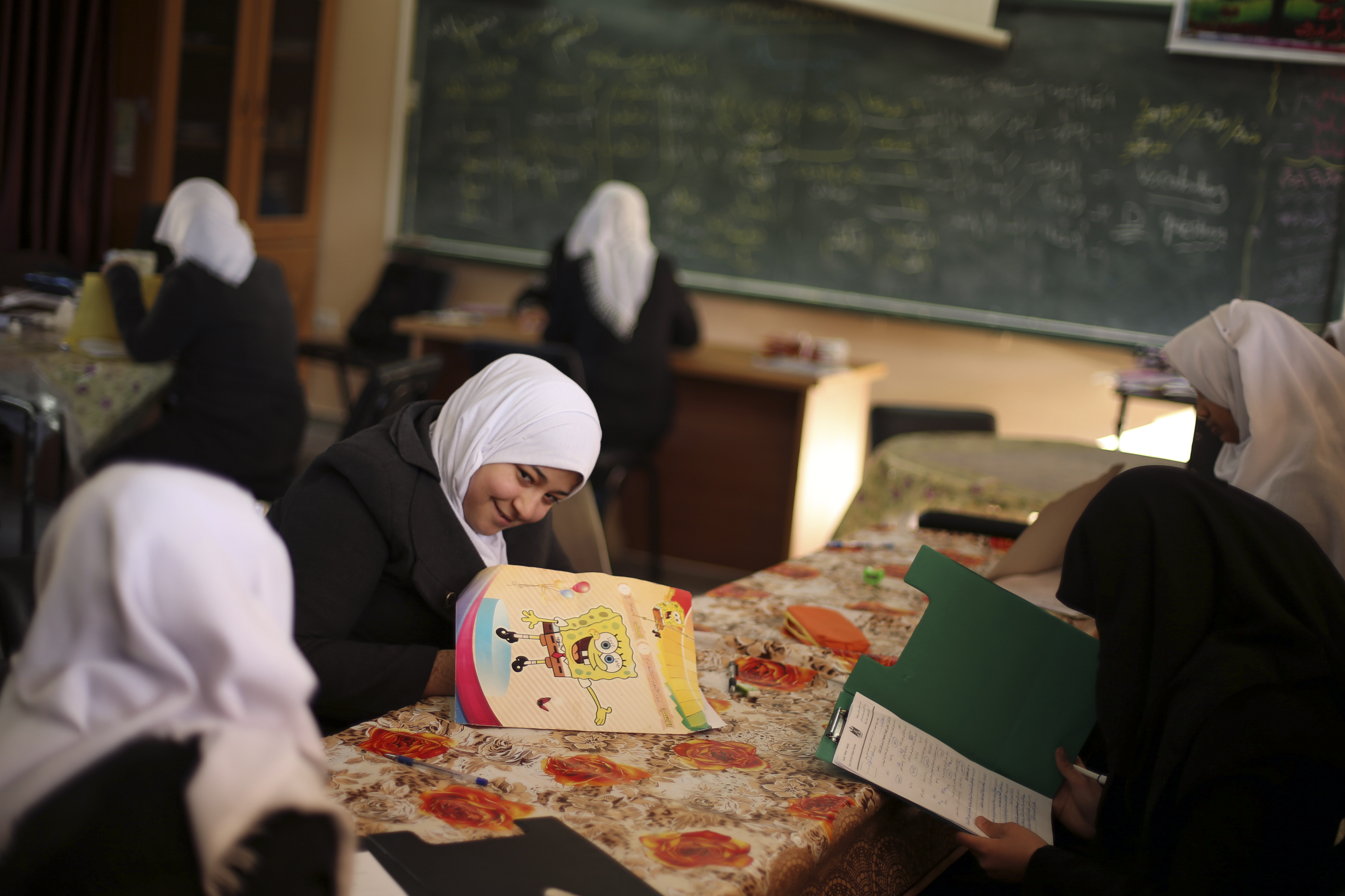 Palestinian girl Manar Al-Shinbari (C), 15, who lost both her legs in what medics said was Israeli shelling at a UN-run school where she was taking refuge during the 50-day war last summer, takes an exam at her school, in Jabaliya refugee camp in the northern Gaza Strip January 13, 2015. Manar's mother and three of her brothers were killed in the same incident. The girl's family house was destroyed by Israeli shelling during the war. REUTERS/Mohammed Salem (GAZA - Tags: POLITICS CIVIL UNREST SOCIETY CONFLICT EDUCATION) - RTR4L8NW