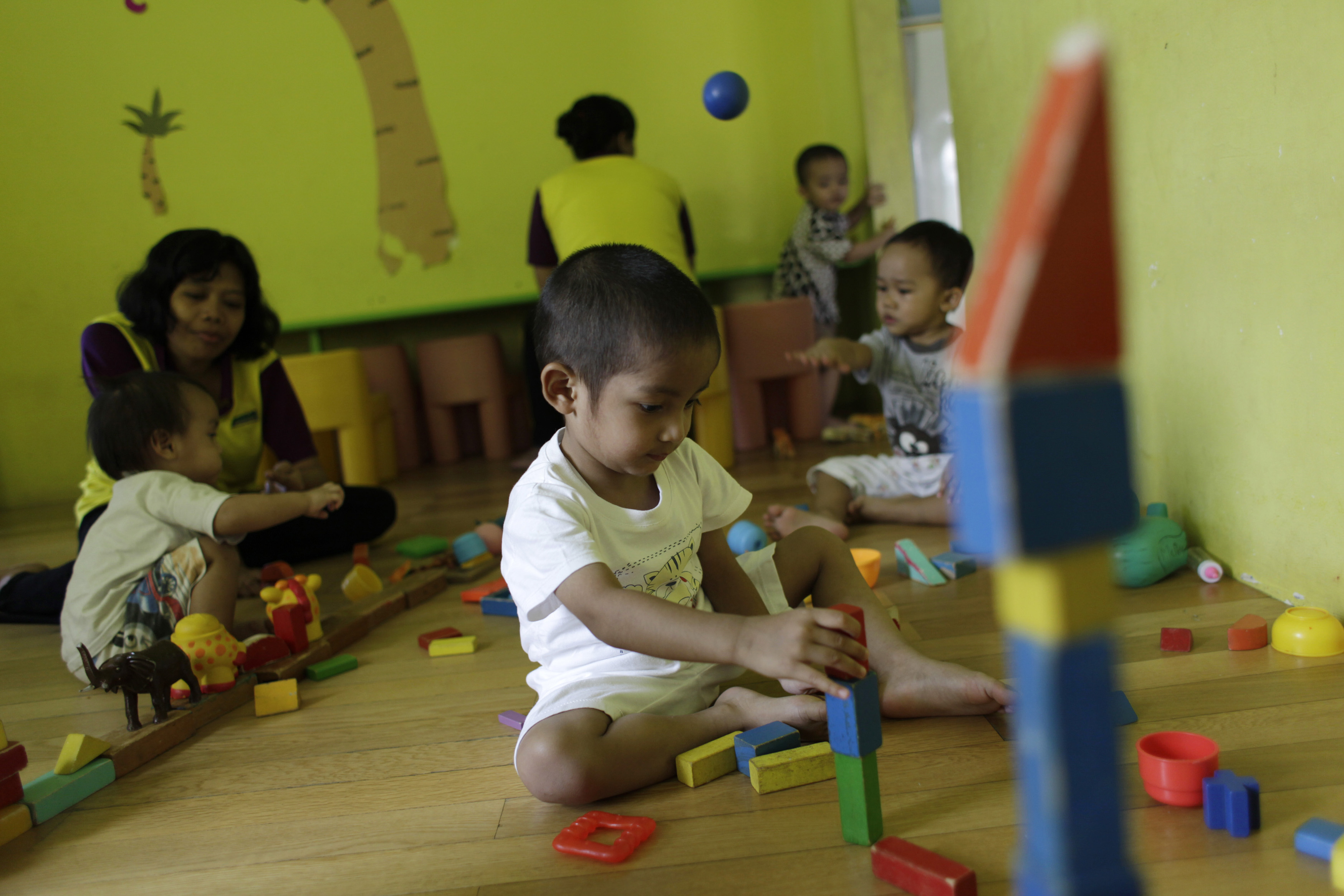 Children play at Keen Kids daycare in Jakarta August 2, 2012. With more and more women going out to work due to more education and middle-class aspirations daycare has become essential for residents of urban Jakarta, much the way it has in the rest of the developed world. Picture taken August 2, 2012. To match story INDONESIA-DAYCARE/   REUTERS/Beawiharta (INDONESIA - Tags: SOCIETY BUSINESS EMPLOYMENT EDUCATION) - RTR3A3M4