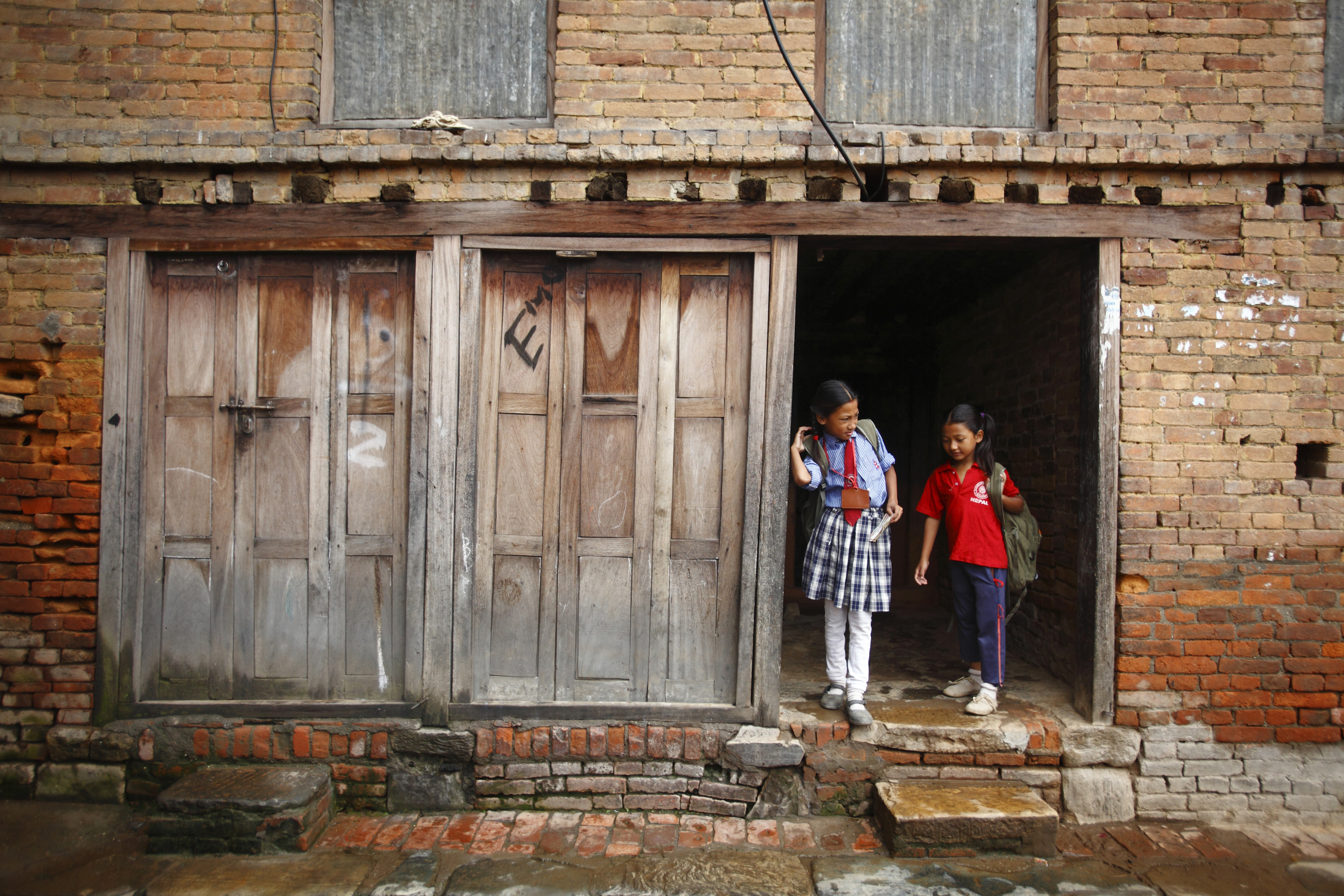 Children walk out from their home as they head towards their school in the ancient city of Bhaktapur, Nepal September 13, 2012. REUTERS/Navesh Chitrakar (NEPAL - Tags: SOCIETY TPX IMAGES OF THE DAY) - RTR37WVH