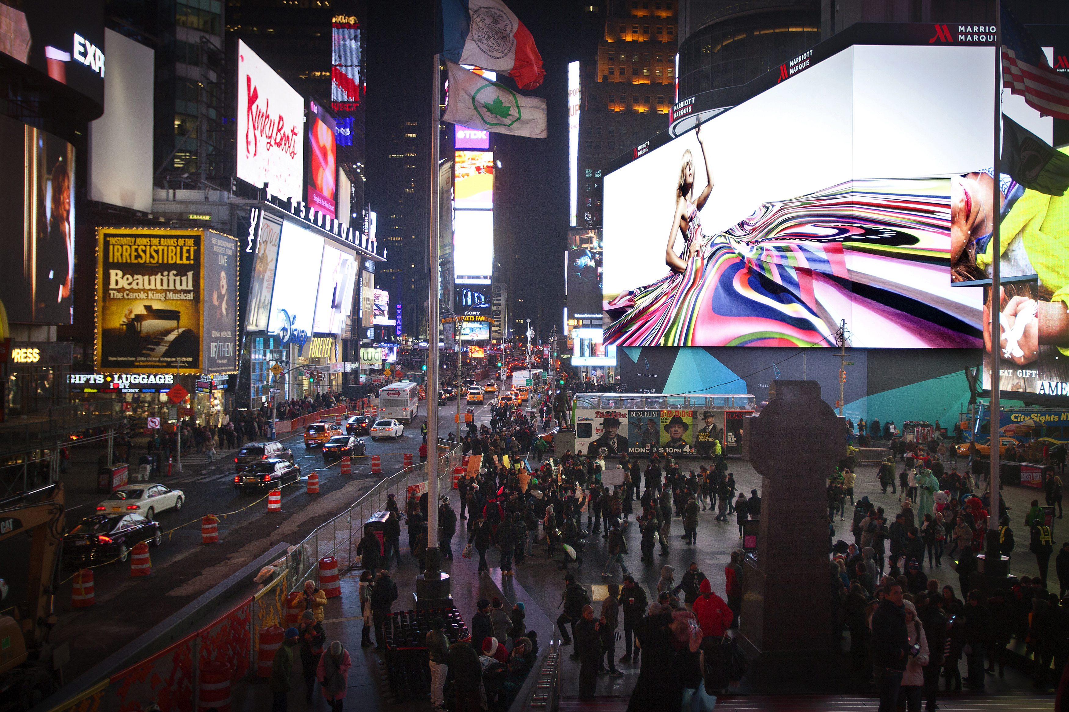 People walk underneath a giant new advertising screen in Times Square, New York, November 20, 2014. The biggest advertising billboard in Times Square history, longer that a football field and eight stories high, which is the world's largest high-definition video display with nearly 24 million LED pixels, lit up for the first time on Tuesday. The rate for a four-week advertising blitz is $2.5 million, according to the New York Times.