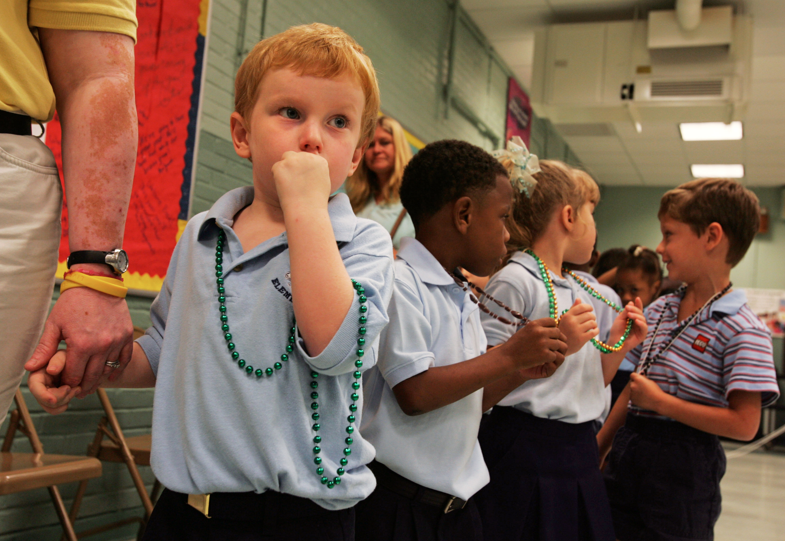 Pre-schooler Cecil Smith (L), 4, holds the hand of a teacher's assistant as he prepares to go to class after he and classmates were given Mardi Gras beads, on the first day of school since Hurricane Katrina hit over a month ago, at an elementary school in Metairie, Louisiana October 3, 2005. Public schools opened throughout Jefferson Parish, including Metairie, a suburb of New Orleans. REUTERS/Lee Celano - RTR18O4R