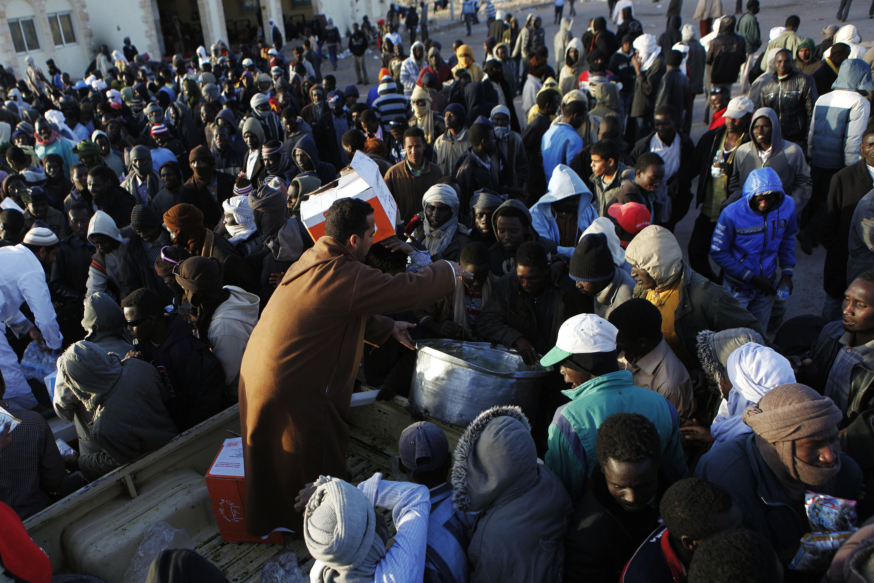 Refugees from sub-Saharan Africa receive food being handed out at the Libya-Egypt border to African workers who fled fighting in eastern Libya, March 16, 2011. REUTERS/Finbarr O'Reilly (EGYPT - Tags: CONFLICT CIVIL UNREST POLITICS) - RTR2JZDX