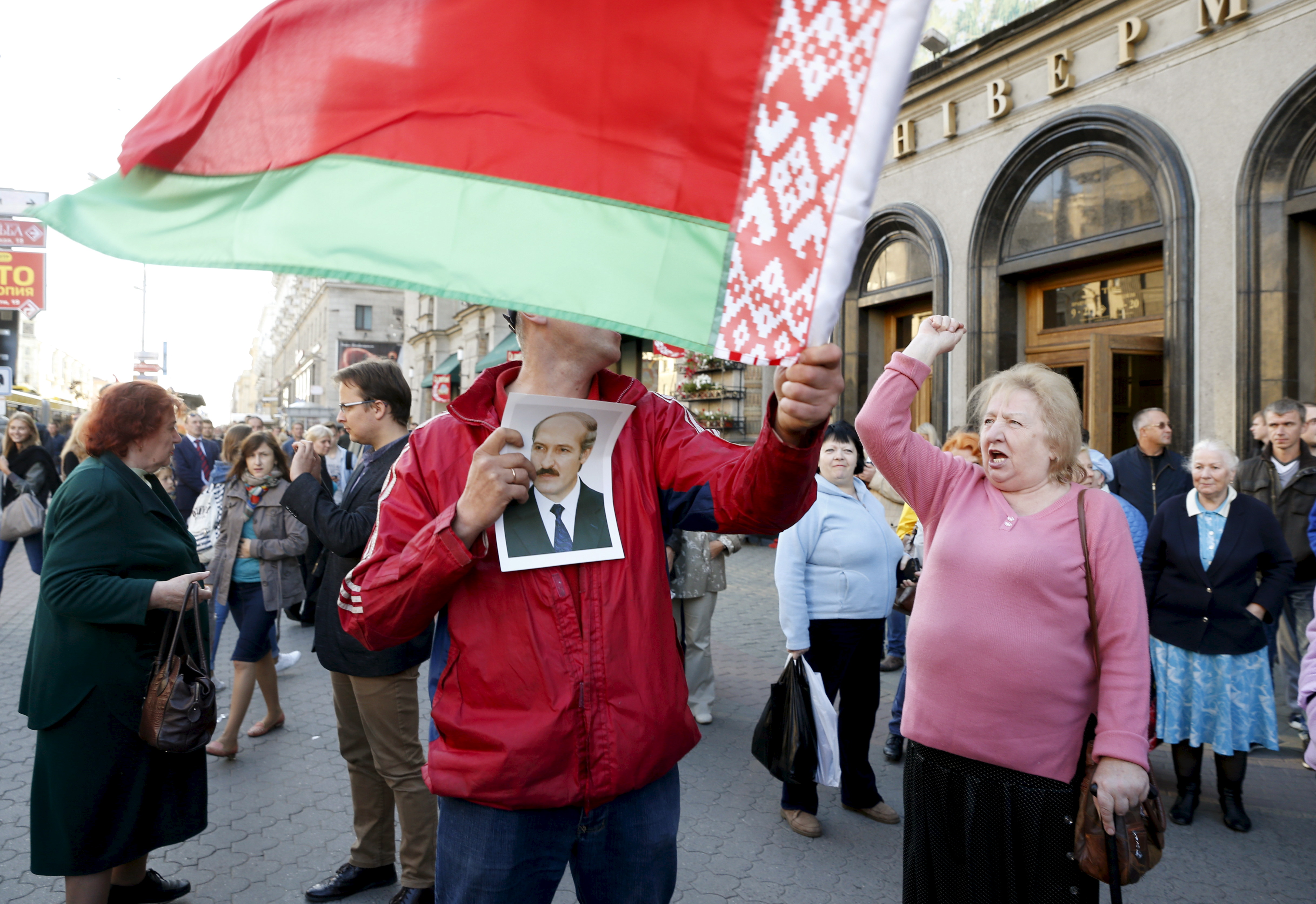 A man holds a portrait of Belarussian President Alexander Lukashenko, who is a candidate in the upcoming presidential elections, and a Belarussian national flag during a meeting between opposition leaders and people, in central Minsk, September 10, 2015. The Belarussian presidential election is scheduled to be held on October 11, 2015. REUTERS/Vasily Fedosenko - RTSILE