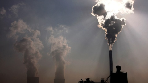 A coal-burning power plant can be seen behind a factory in the city of Baotou, in China's Inner Mongolia Autonomous Region October 31, 2010.     REUTERS/David Gray/File Photo   - RTSPKVR