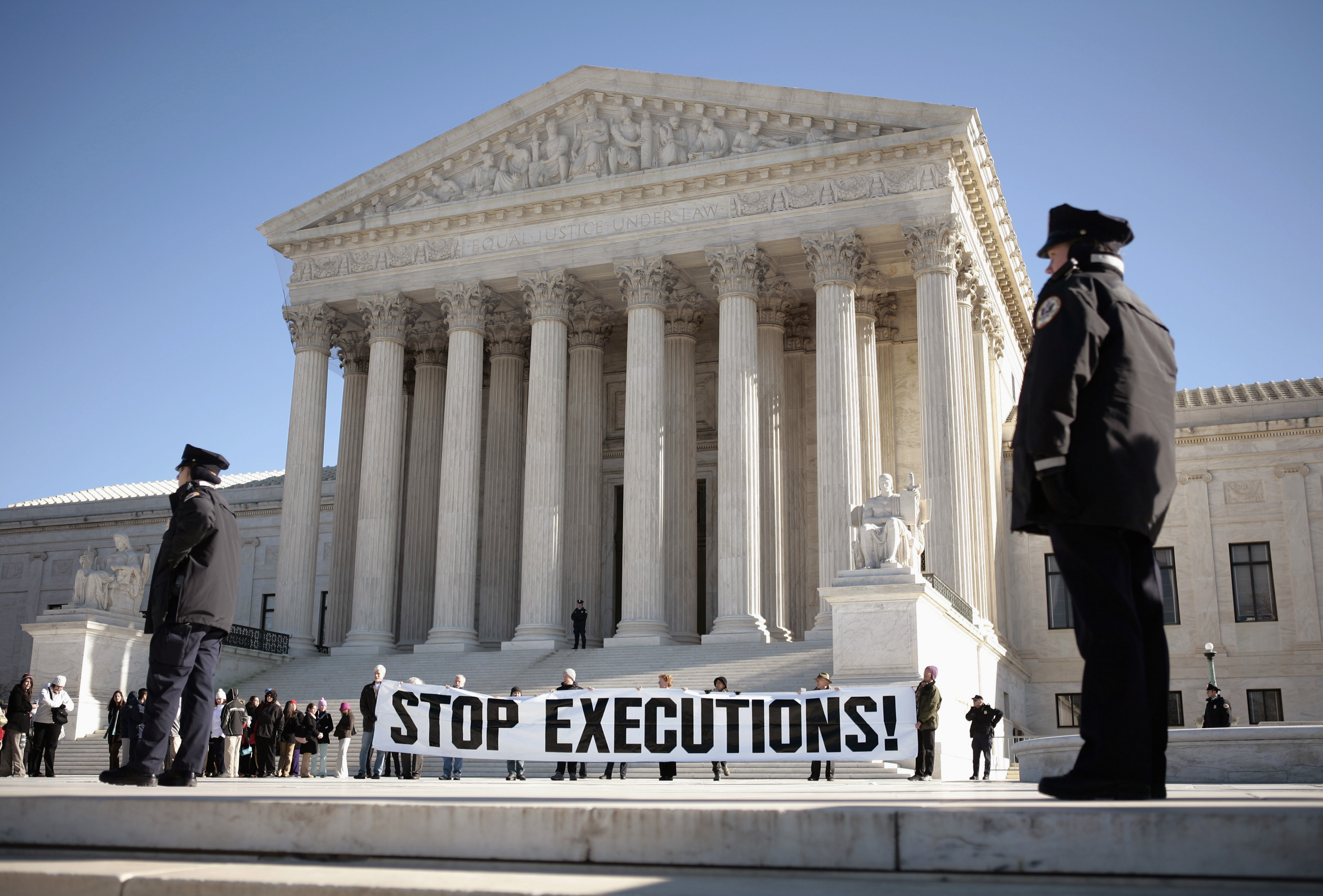 FILE PHOTO: Protesters calling for an end to the death penalty unfurl a banner before police arrest them outside the U.S. Supreme Court in Washington January 17, 2007. REUTERS/Jason Reed/File Photo - RTSFK7B