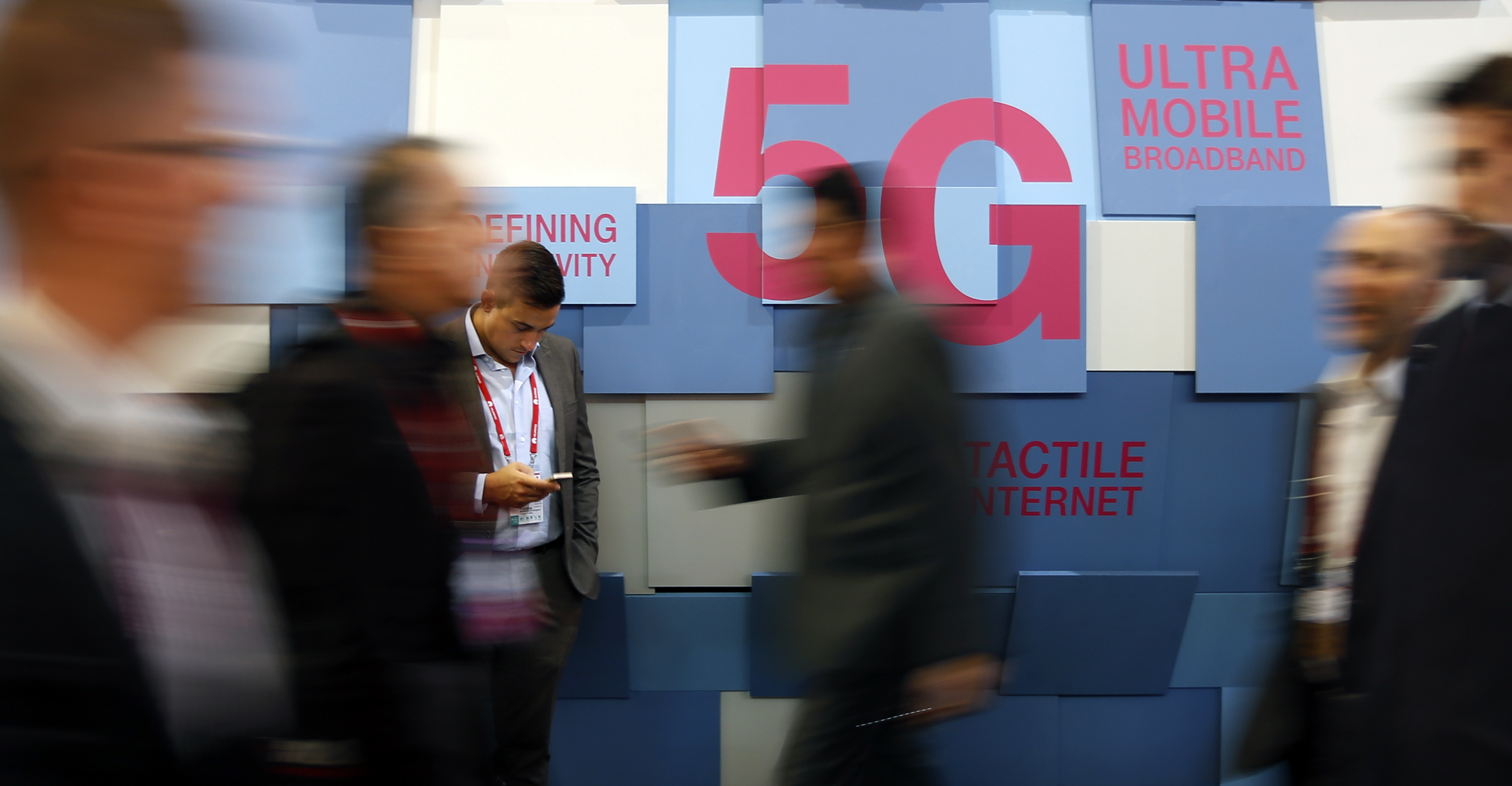 People walk past a 5G banner during the Mobile World Congress in Barcelona, Spain