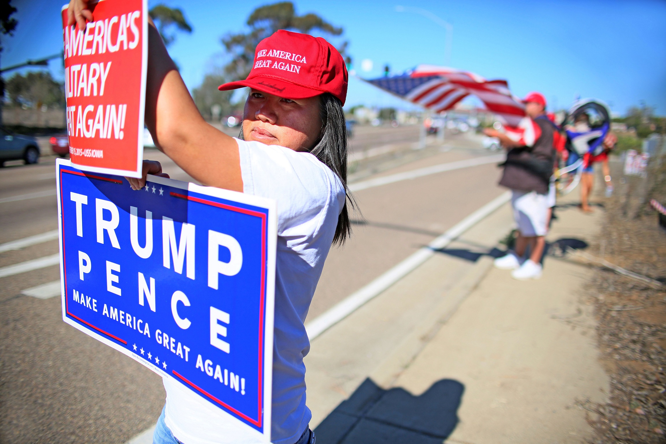 Demonstrator Ly Kou holds a sign along with others in support of President elect Donald Trump outside of Camp Pendleton in Oceanside, California U.S. November 11, 2016. REUTERS/Sandy Huffaker - RTX2TA8C
