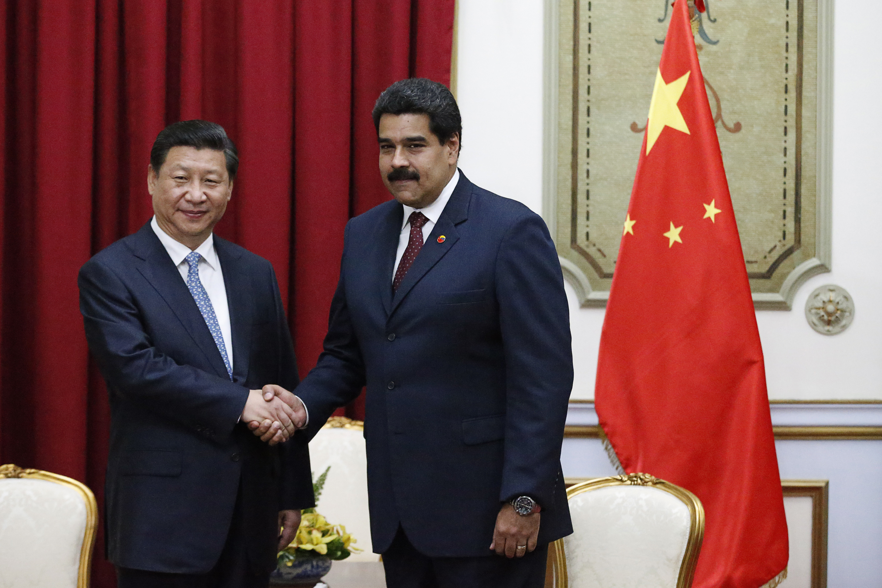 China's President Xi Jinping (L) shakes hands with Venezuela's President Nicolas Maduro at a meeting in Miraflores Palace in Caracas July 20, 2014. REUTERS/Jorge Silva (VENEZUELA - Tags: POLITICS) - RTR3ZG6I