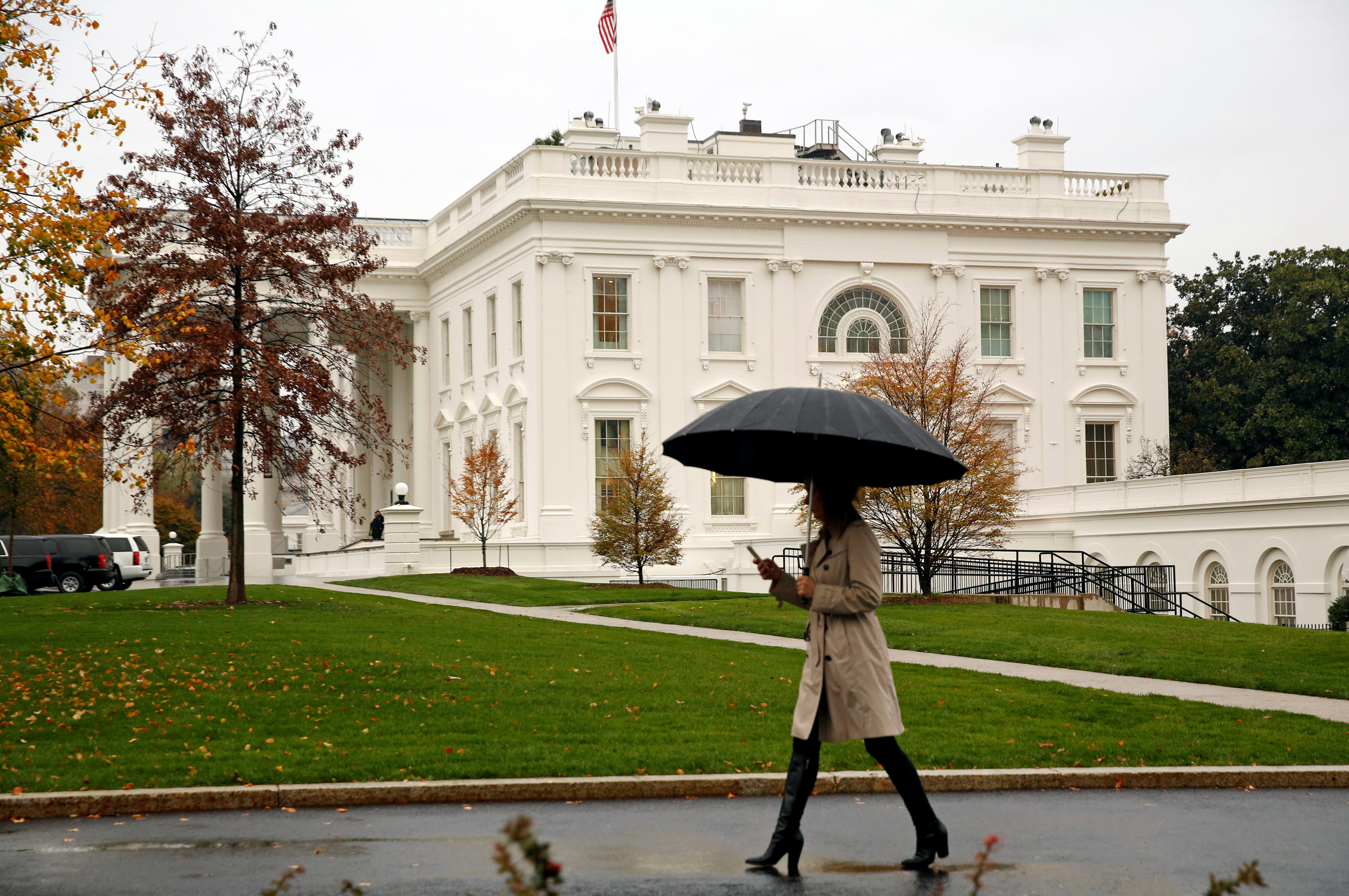 Woman holds an umbrella at the White House in Washington
