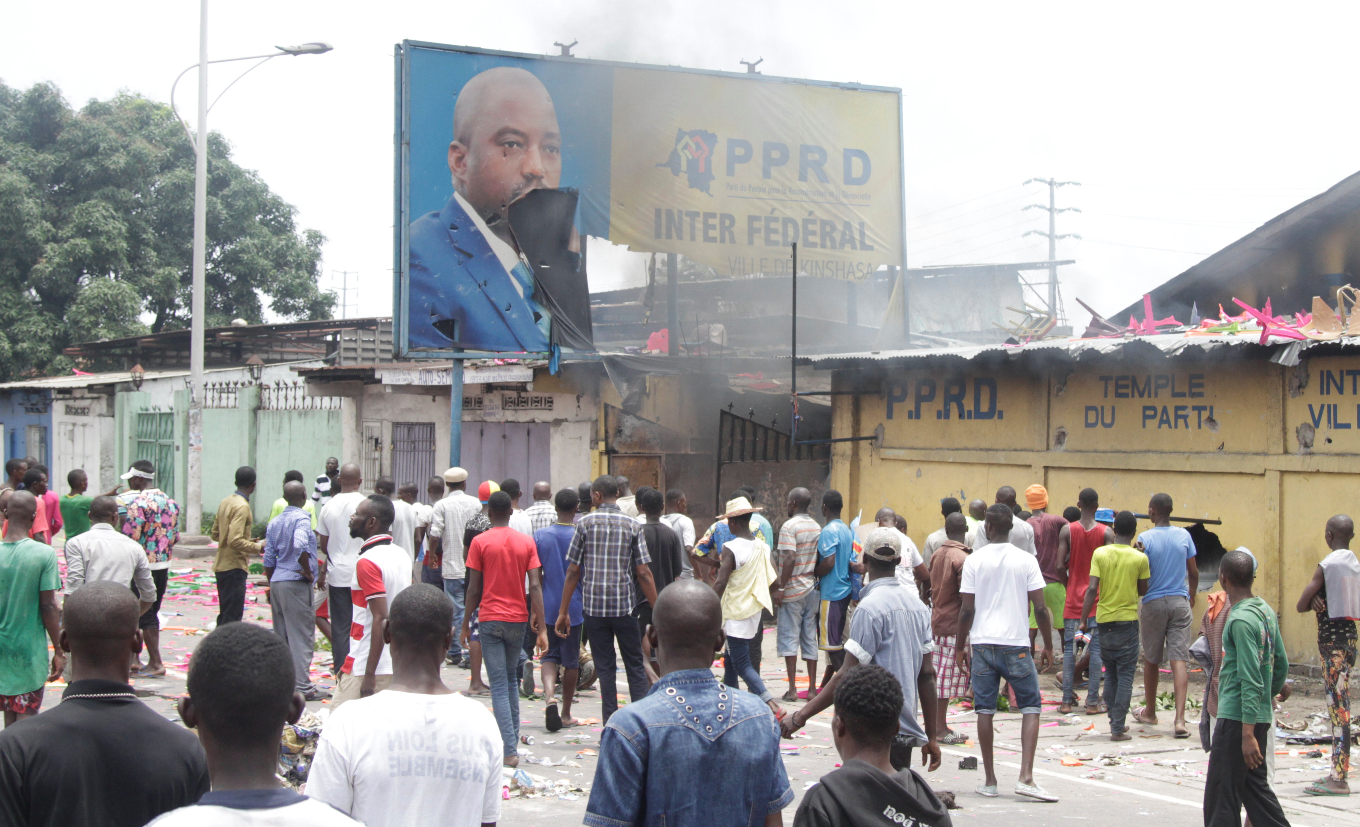 Congolese opposition supporters chant slogans as they destroy the billboard of President Joseph Kabila during a march to press the President to step down in the Democratic Republic of Congo's capital Kinshasa, September 19, 2016. REUTERS/Kenny Katombe/File Photo - RTSQDV6
