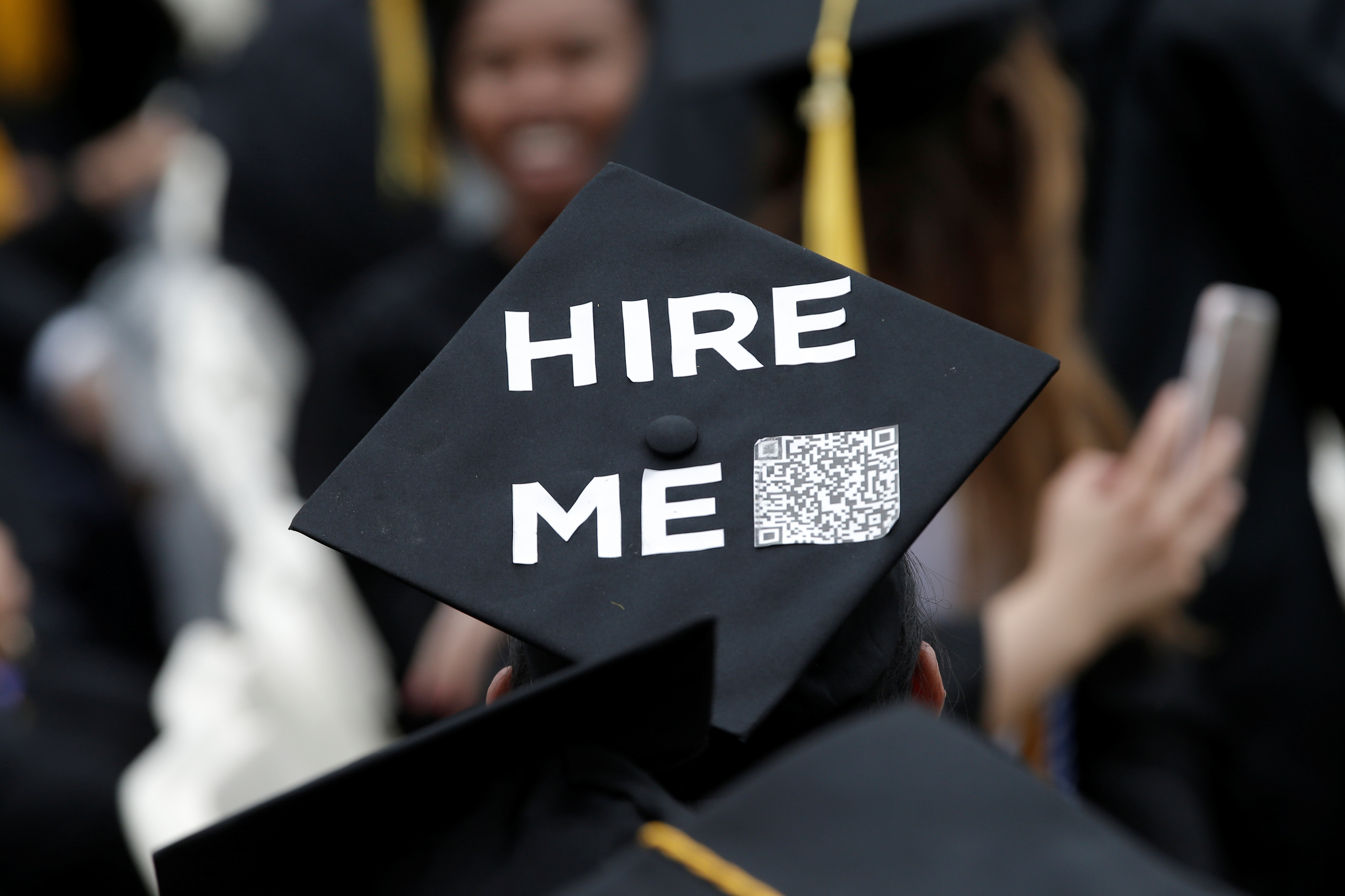 "A graduating student of the City College of New York wears a message on his cap, saying ""Hire me."""