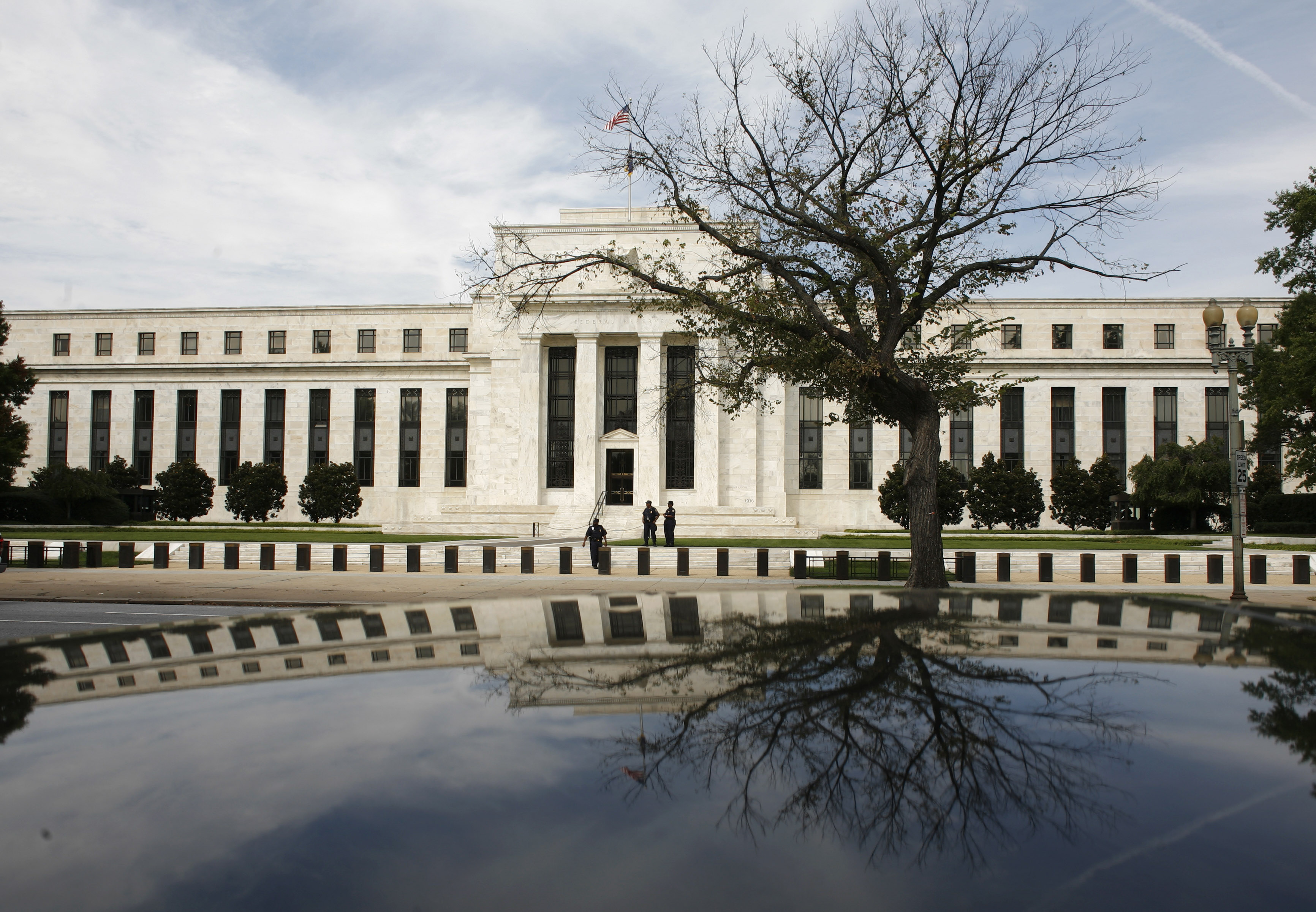 The Federal Reserve Building is reflected on a car in Washington