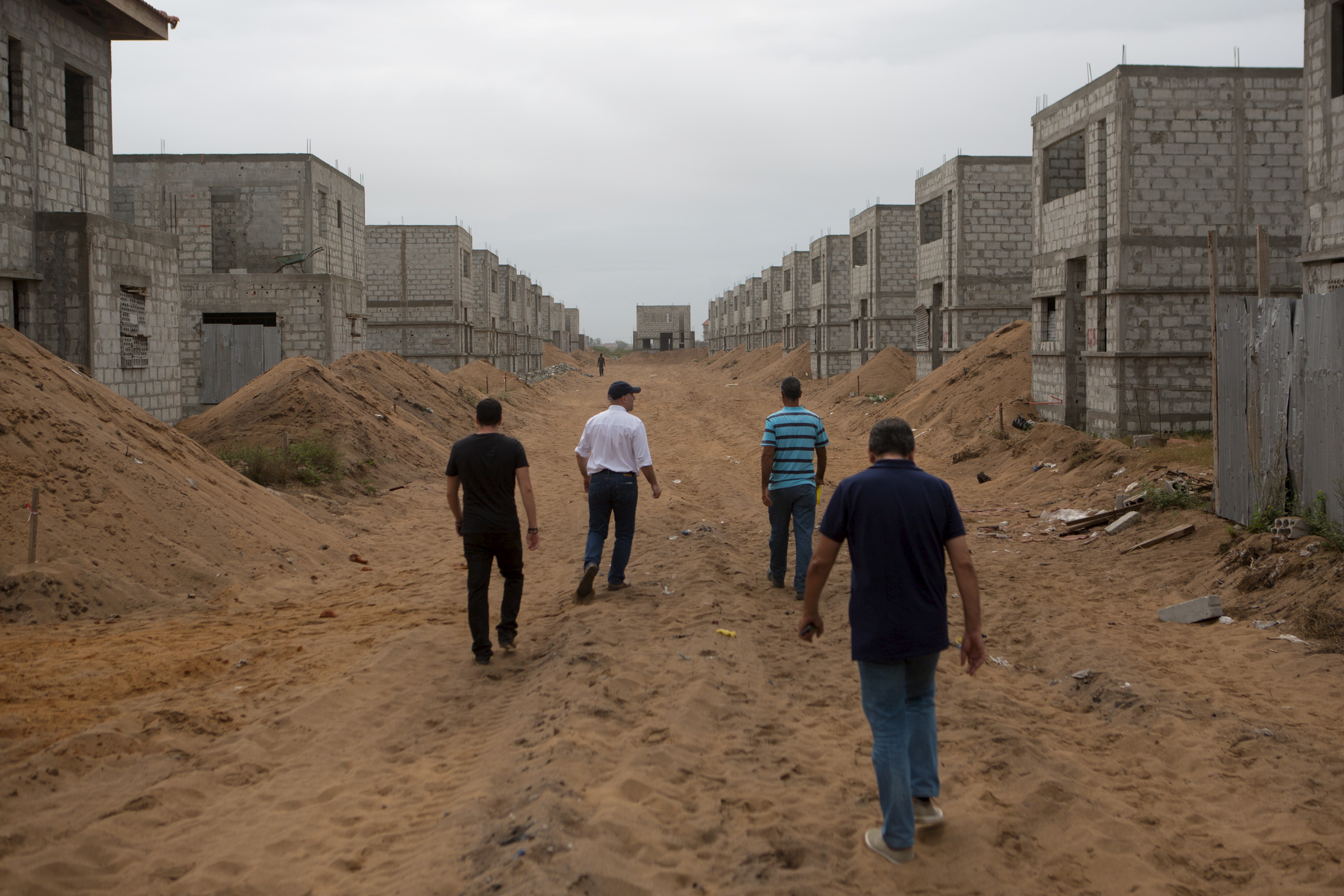 """Chadi Srour (in white shirt), technical director of real estate company Sipim, walks at a Sipim development site with his colleagues in Grand Bassam, Ivory Coast, September 15, 2015. From Abidjan's packed airport arrivals hall to the buildings mushrooming across the capital, Ivory Coast is booming, a rare African bright spot as the world's biggest cocoa producer bounces back from a 2011 civil war. Buyers of luxury apartments include Ivorians living overseas, while promoters from Morocco, Turkey and China are attracted by tax breaks. Elections - the source of national unrest four years ago - are due in a month but there is no let-up in investment given expectations of an easy victory for incumbent Alassane Ouattara. The government predicts 9.6 percent growth this year, making the former French colony the standout performer on a continent hammered by a slump in commodity prices, capital outflows and tumbling currencies.    REUTERS/Joe PenneyPICTURE 17 OF 33 FOR WIDER IMAGE STORY """"IVORY COAST IS BOOMING"""". SEARCH """"BOOMING PENNEY"""" FOR ALL IMAGES - RTX1SEEB"""