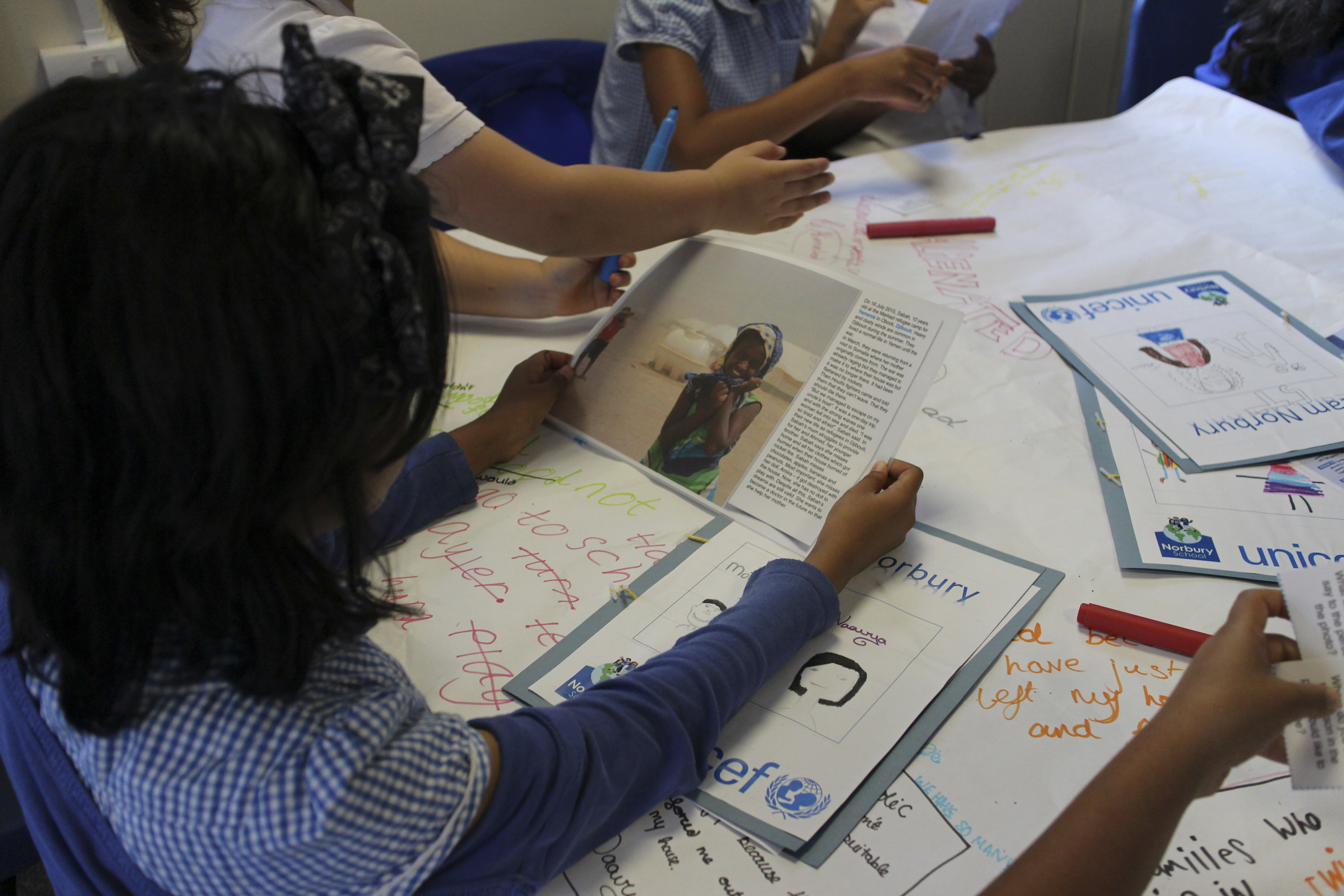 Primary school children, including those with refugee backgrounds, read real-life stories about refugees during a classroom lesson about the refugee crisis at Norbury School in Harrow, London, Britain July 15, 2016. Picture taken July 15, 2016.  Thomson Reuters Foundation/Lin Taylor - RTSIU5X