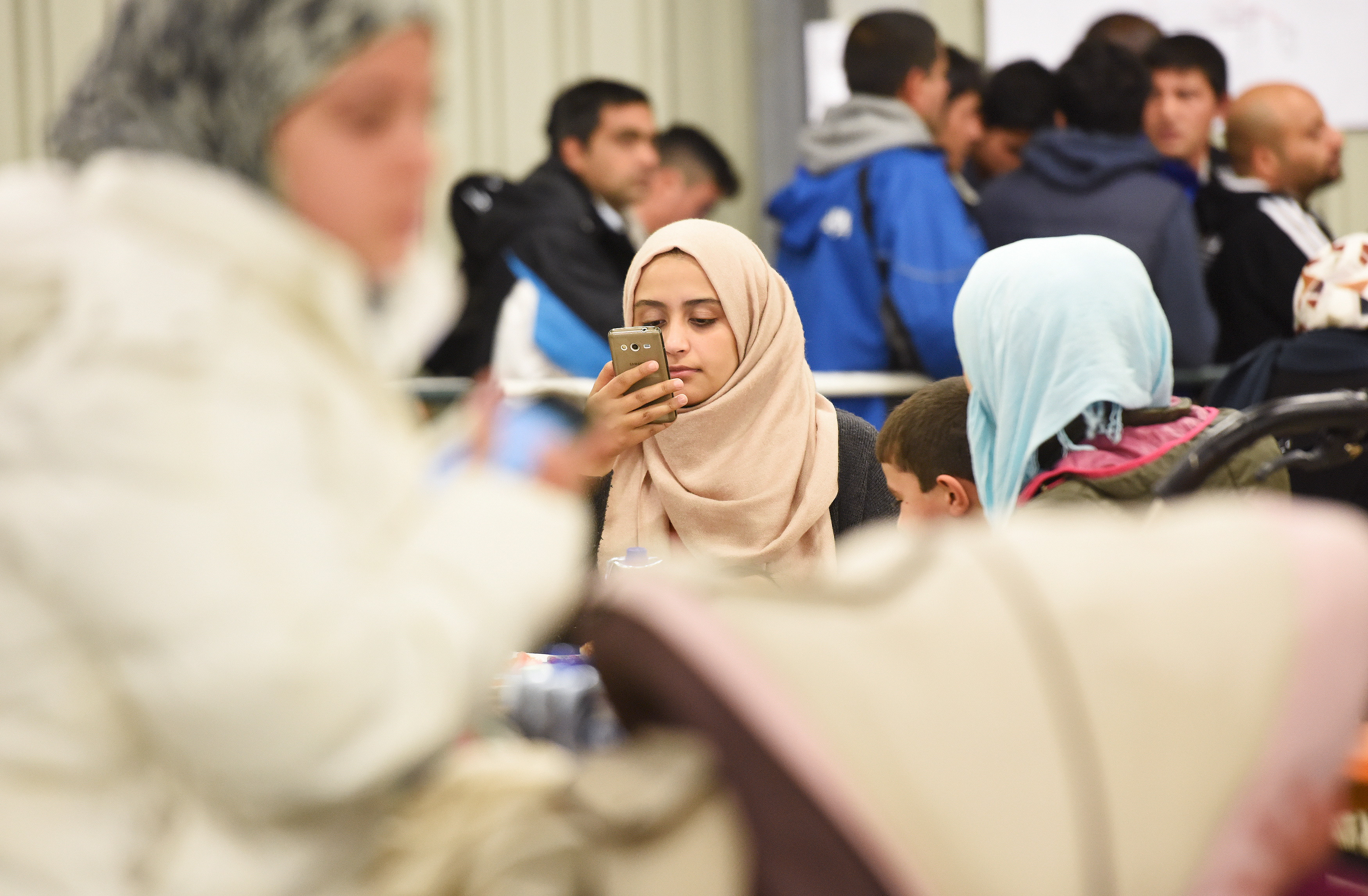 A migrant uses her cell phone in a canteen in a refugee camp in Celle, Lower-Saxony, Germany October 15, 2015. With the approach of winter, authorities are scrambling to find warm places to stay for the thousands of refugees streaming into Germany every day. In desperation, they have turned to sports halls, youth hostels and empty office buildings. But as these options dry up, tent cities have become the fall-back plan: despite falling temperatures, a survey by German newspaper Die Welt showed at least 42,000 refugees were still living in tents. Picture taken October 15, 2015. To match Insight EUROPE-MIGRANTS/GERMANY-WINTER REUTERS/Fabian Bimmer - RTS4YGV