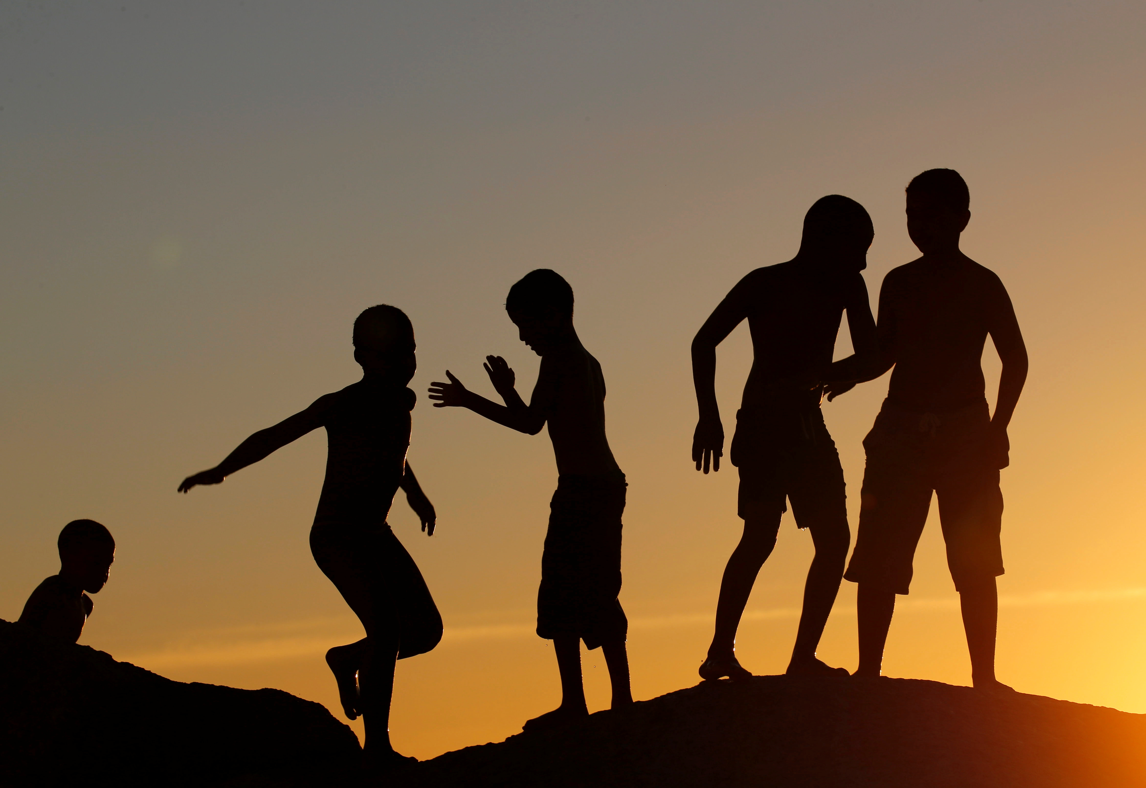 Children play on a rocky outcrop as temperatures soar at Camps Bay beach in Cape Town, South Africa, December 11, 2016.   REUTERS/Mike Hutchings - RTX2UK5J