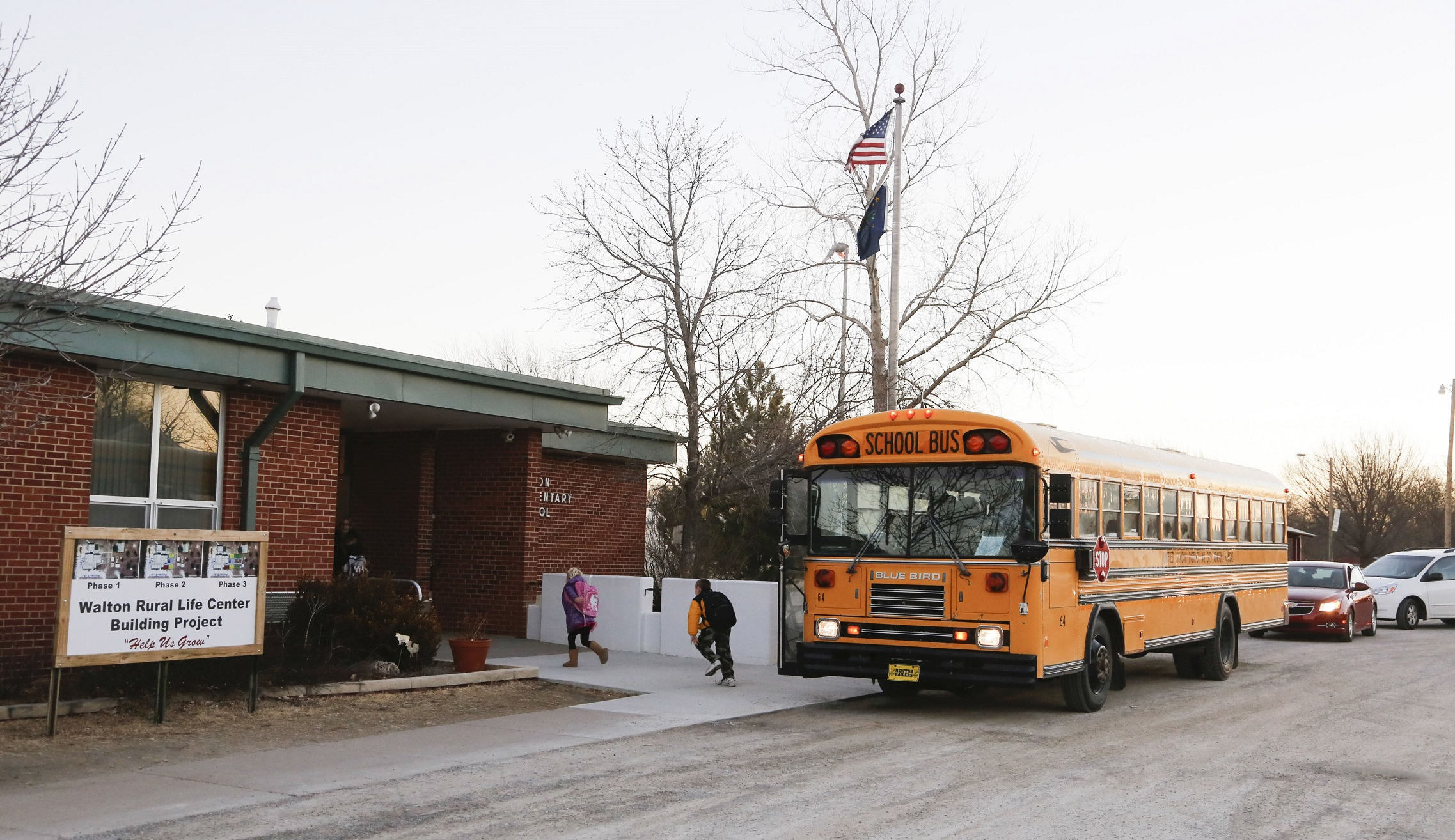 Students arrive at the Walton Rural Life Center Elementary School, in Walton, Kansas, January 18, 2013. Students at the school do farm chores at the beginning of each school day. The Walton Rural Life Center - a kindergarten through fourth grade charter school in rural Kansas - uses agriculture to teach students about math, science, economics. REUTERS/Jeff Tuttle (UNITED STATES - Tags: EDUCATION AGRICULTURE SOCIETY) - RTR3DVPU