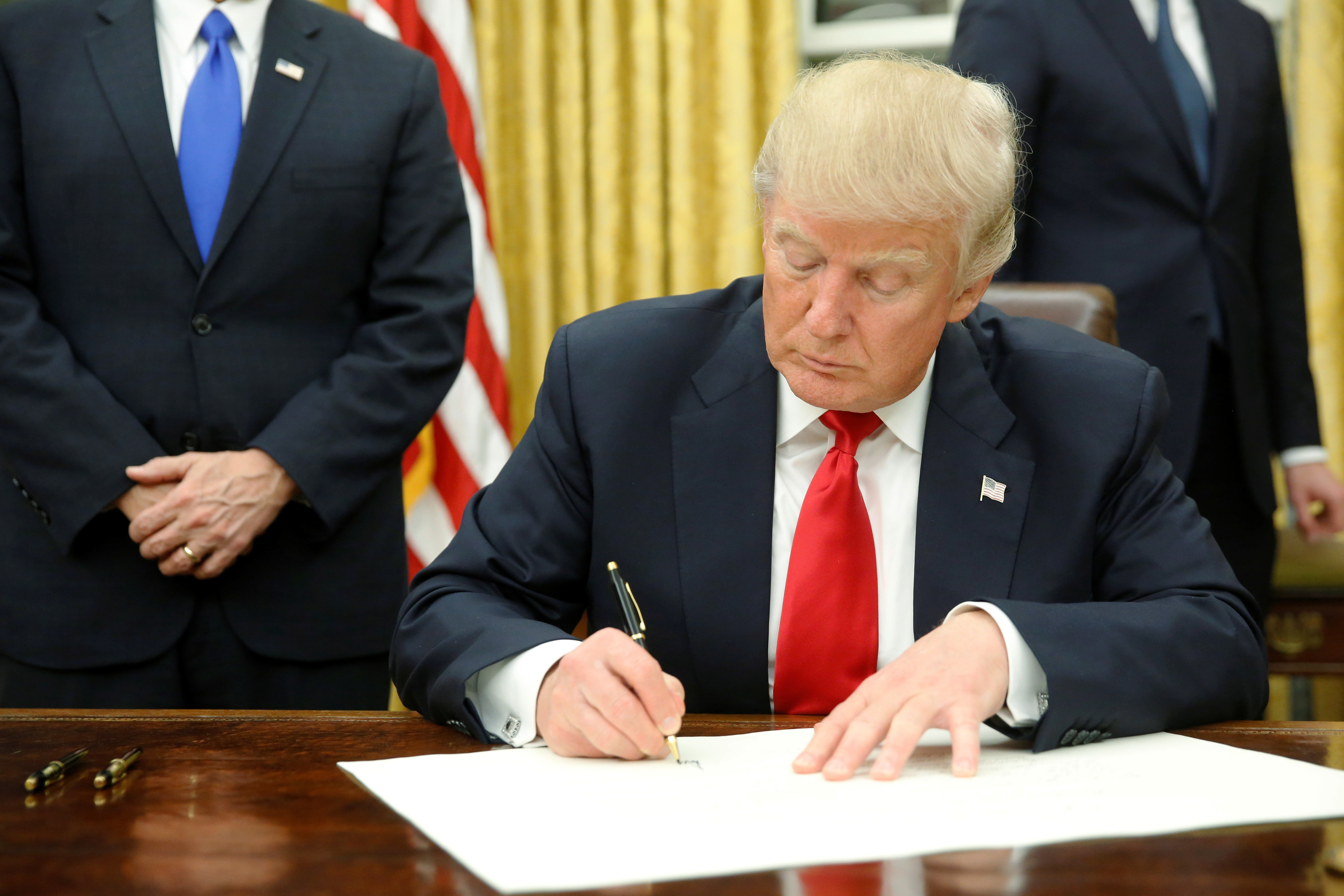 U.S. President Donald Trump signs his first executive orders in the Oval Office in Washington, U.S. January 20, 2017. REUTERS/Jonathan Ernst - RTSWLUX
