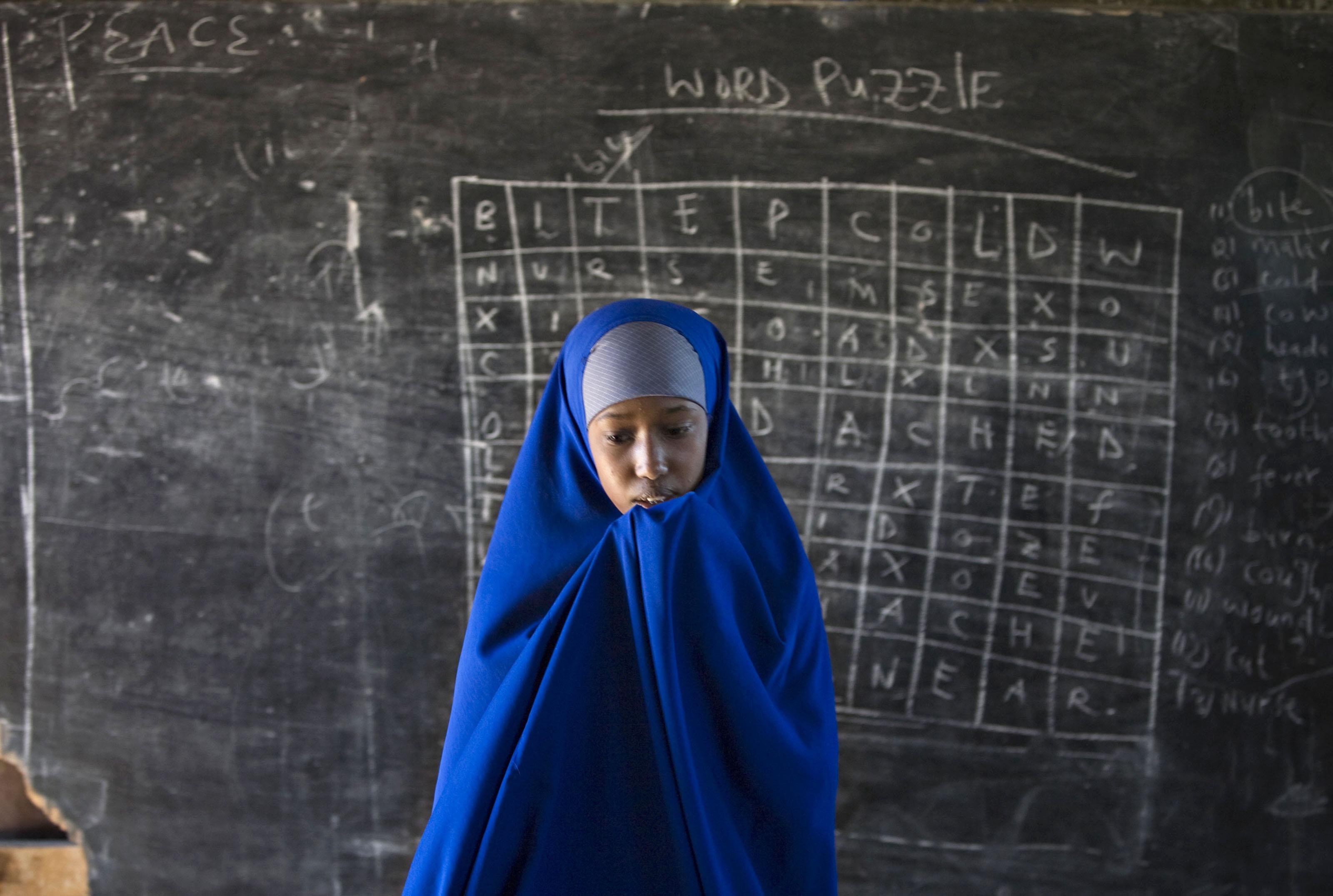 Somali refugee girl walks in front of a blackboard at Hagadera camp in Dadaab in northeastern Kenya