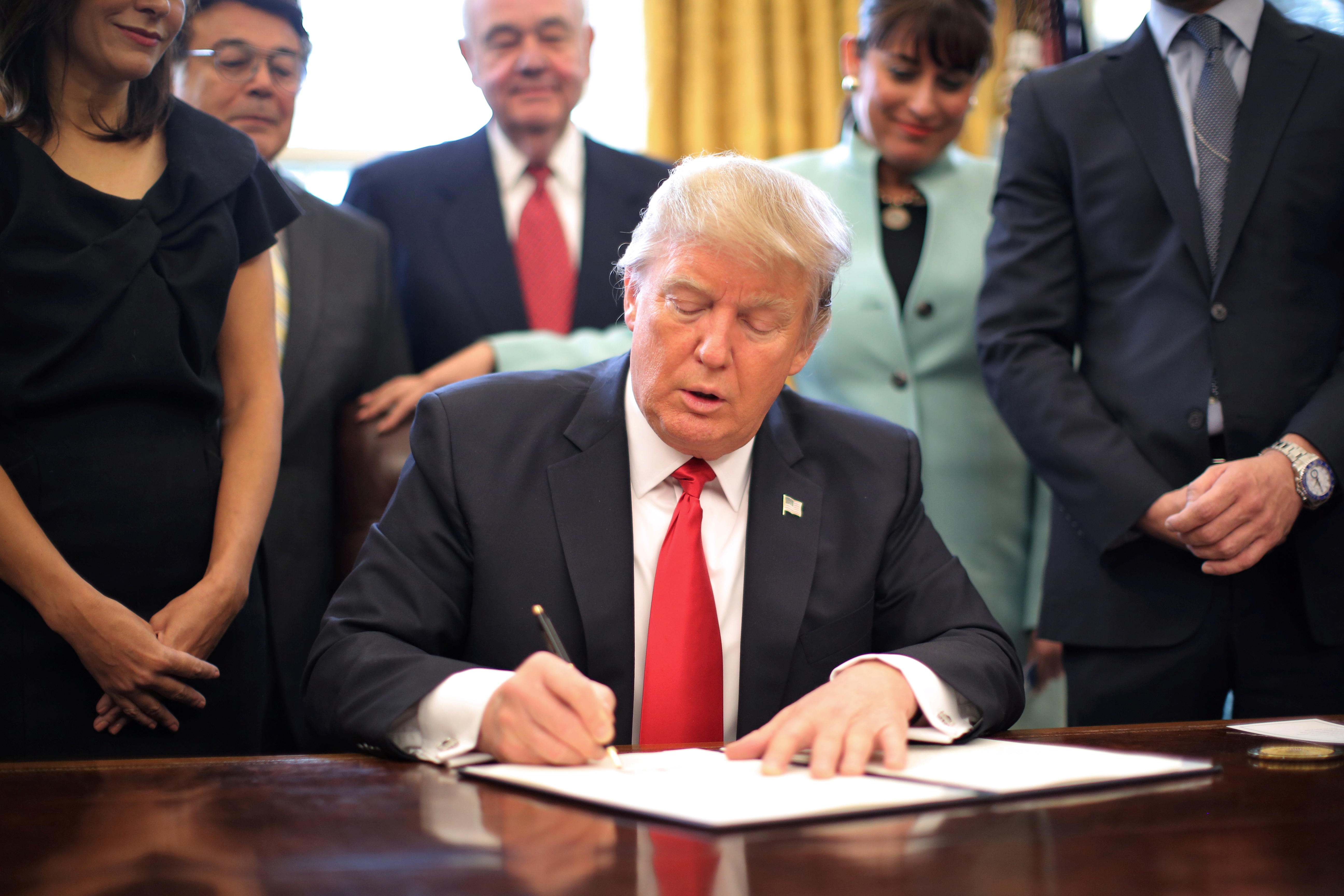 U.S. President Donald Trump signs an executive order cutting regulations, accompanied by small business leaders at the Oval Office of the White House in Washington U.S.