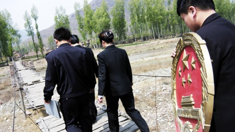 Chinese mobile court officials walk towards a village to convene a court in Zuoquan County, north China's Shanxi province, May 10, 2005. Two mobile courts were established in August 2002 in Zuoquan to serve the local people in remote and mountainous regions. According to China's law, the national emblem shall be hung in the courtrooms of the people's courts at various levels. Picture taken on May 10, 2005. CHINA OUT REUTERS/China Newsphoto  SUN/TZ - RTRAQVR
