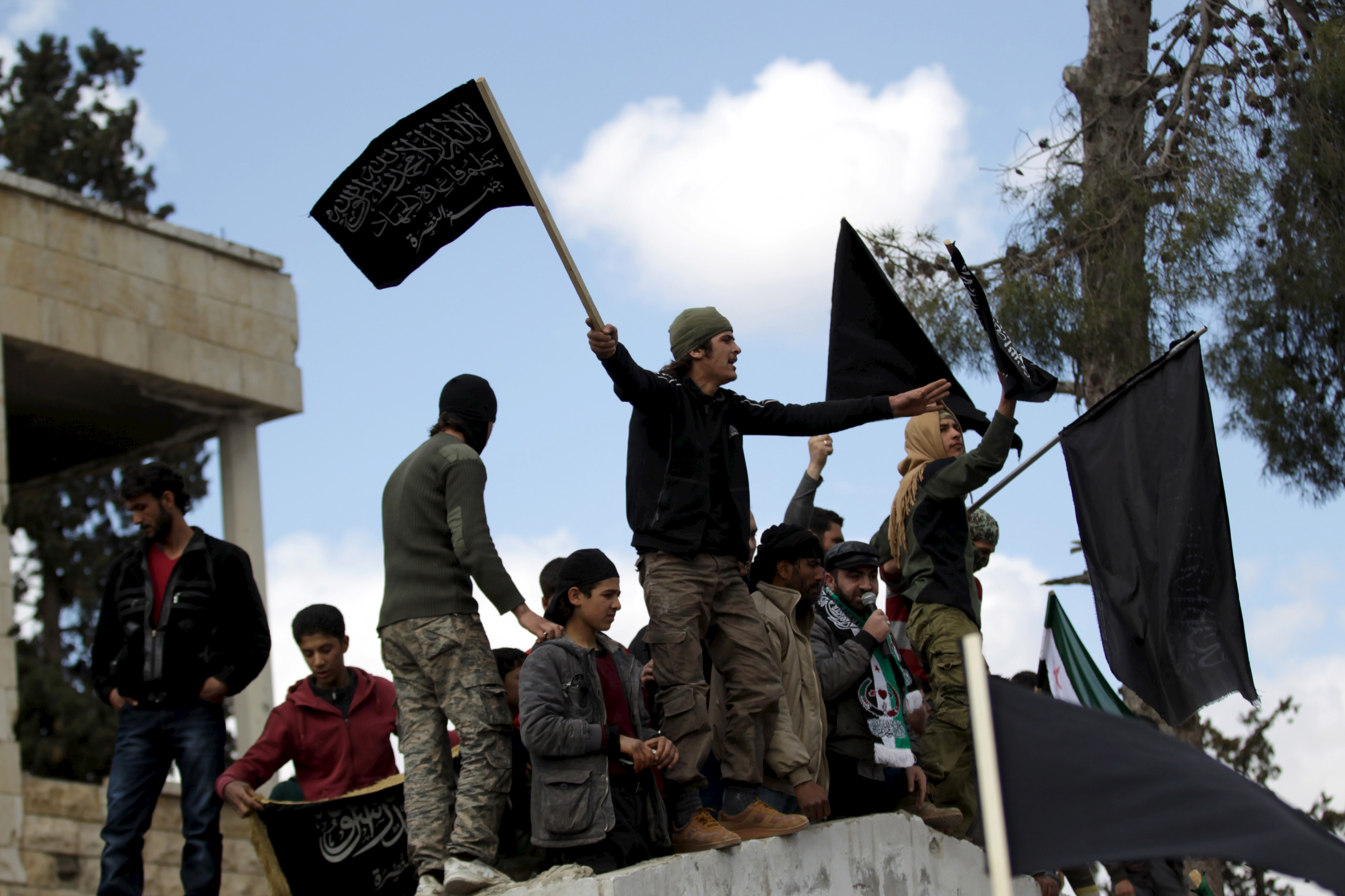 Protesters carry Nusra Front flags and shout slogans during an anti-government protest after Friday prayers in the town of Marat Numan in Idlib province, Syria, March 11, 2016. REUTERS/Khalil Ashawi - RTSAD3R