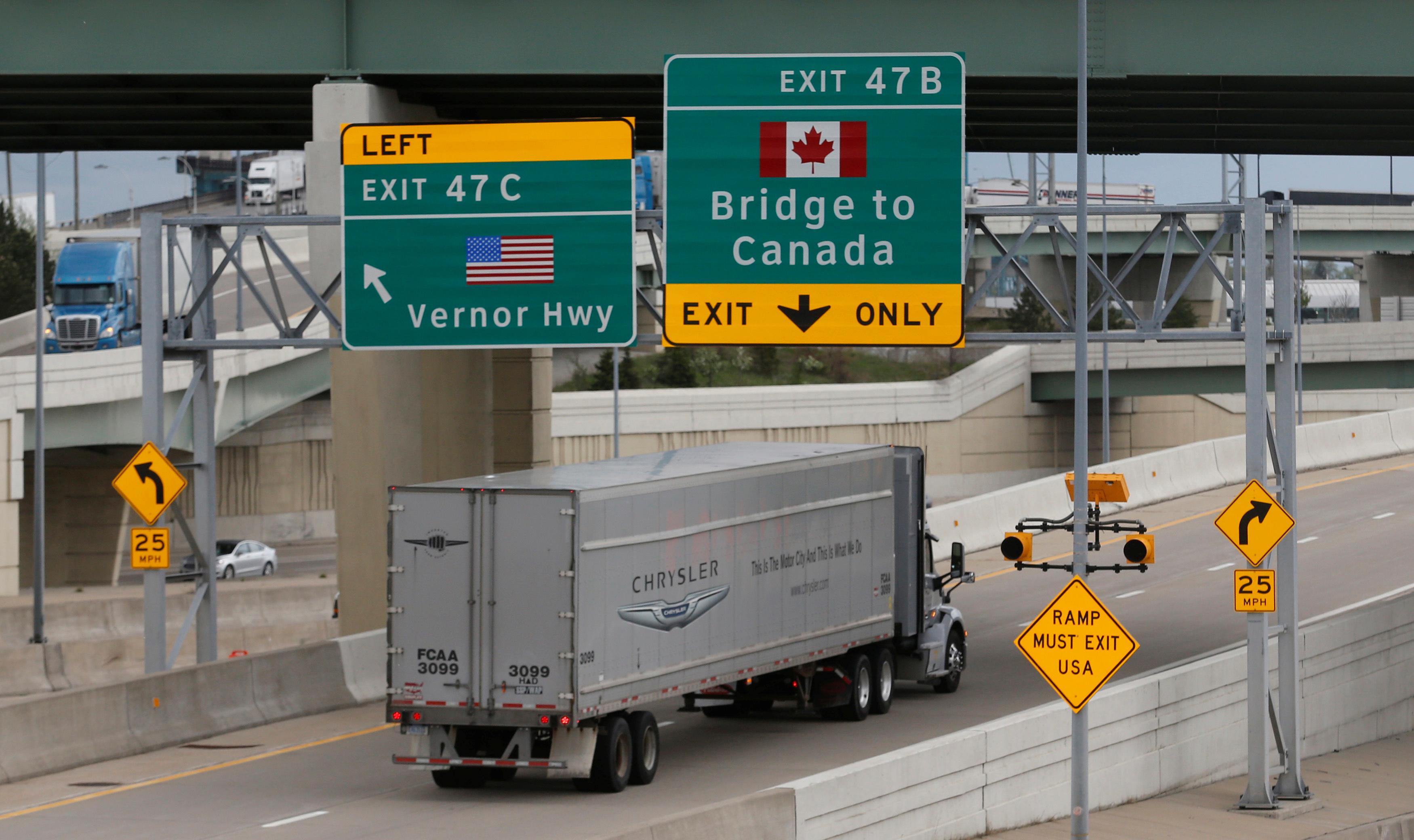 Semi trucks headed for Windsor, Ontario, exit onto the lane towards the Ambassador bridge in Detroit, Michigan, U.S., April 26, 2017.  REUTERS/Rebecca Cook - RTS148ZY