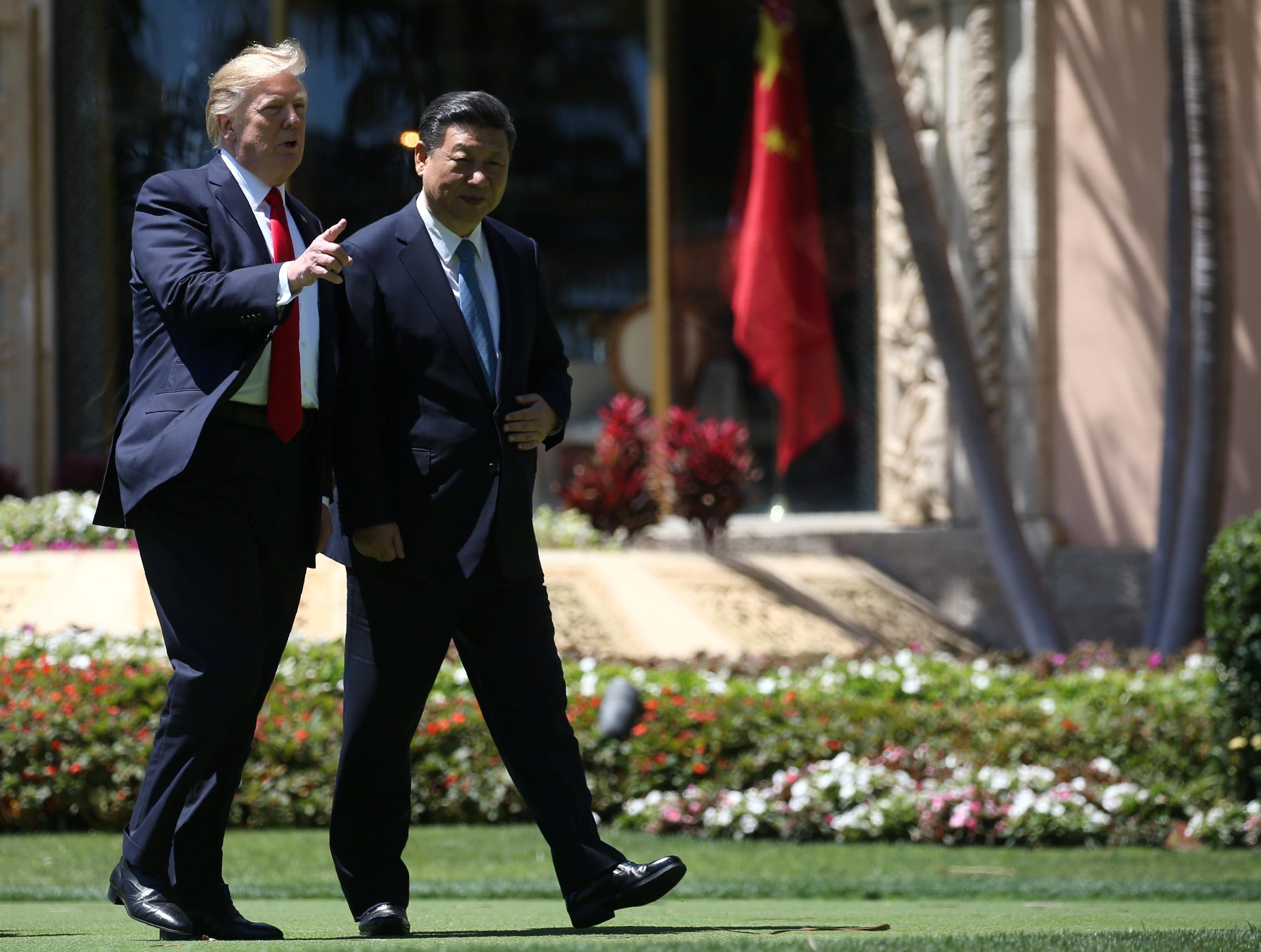 U.S. President Donald Trump (L) and China's President Xi Jinping take a walk together after a bilateral meeting at Trump's Mar-a-Lago estate in Palm Beach, Florida, U.S., April 7, 2017. REUTERS/Carlos Barria