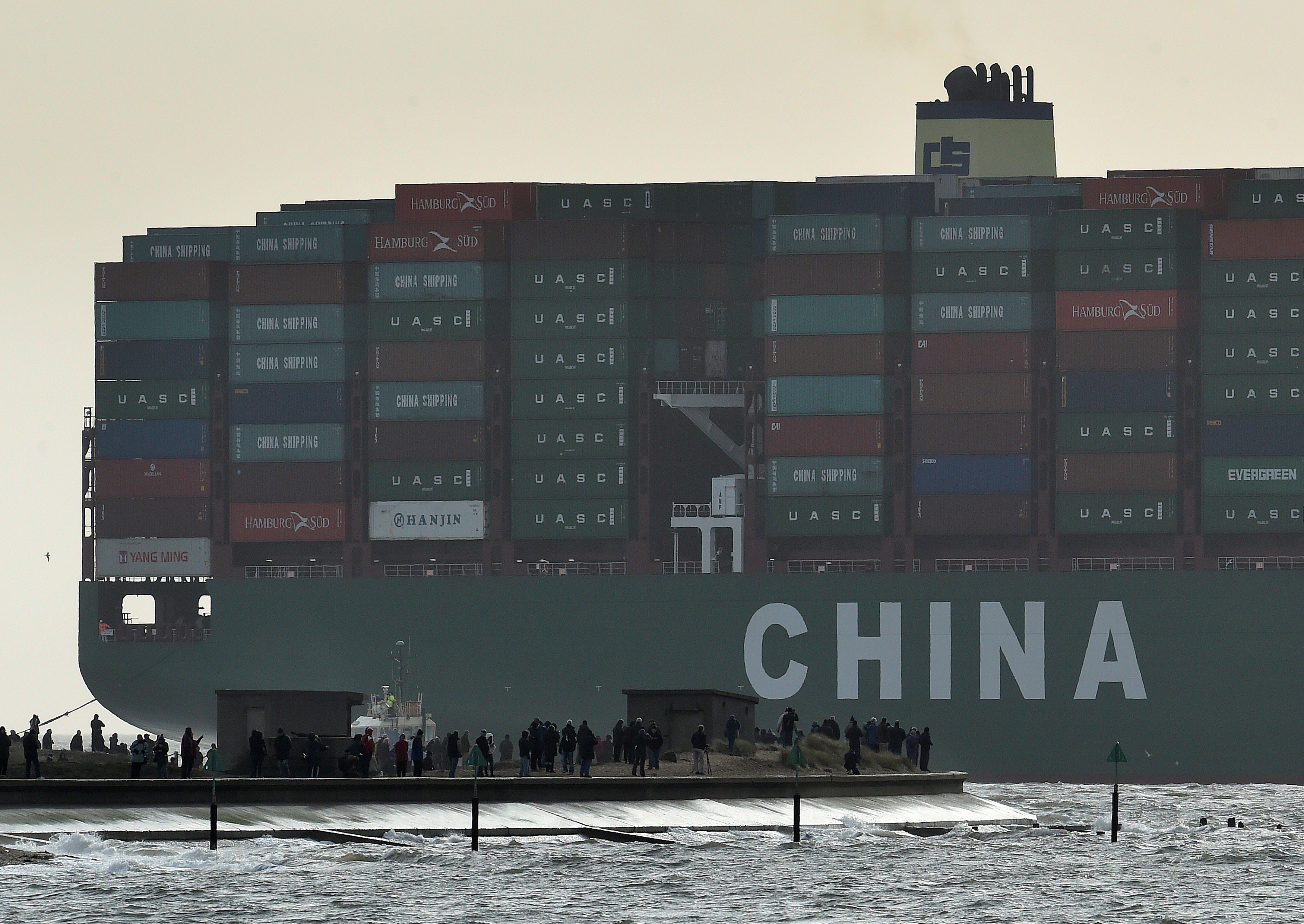 Onlookers watch from a harbour wall as the largest container ship in world, CSCL Globe, docks during its maiden voyage, at the port of Felixstowe in south east England, January 7, 2015. REUTERS/Toby Melville/File Photo