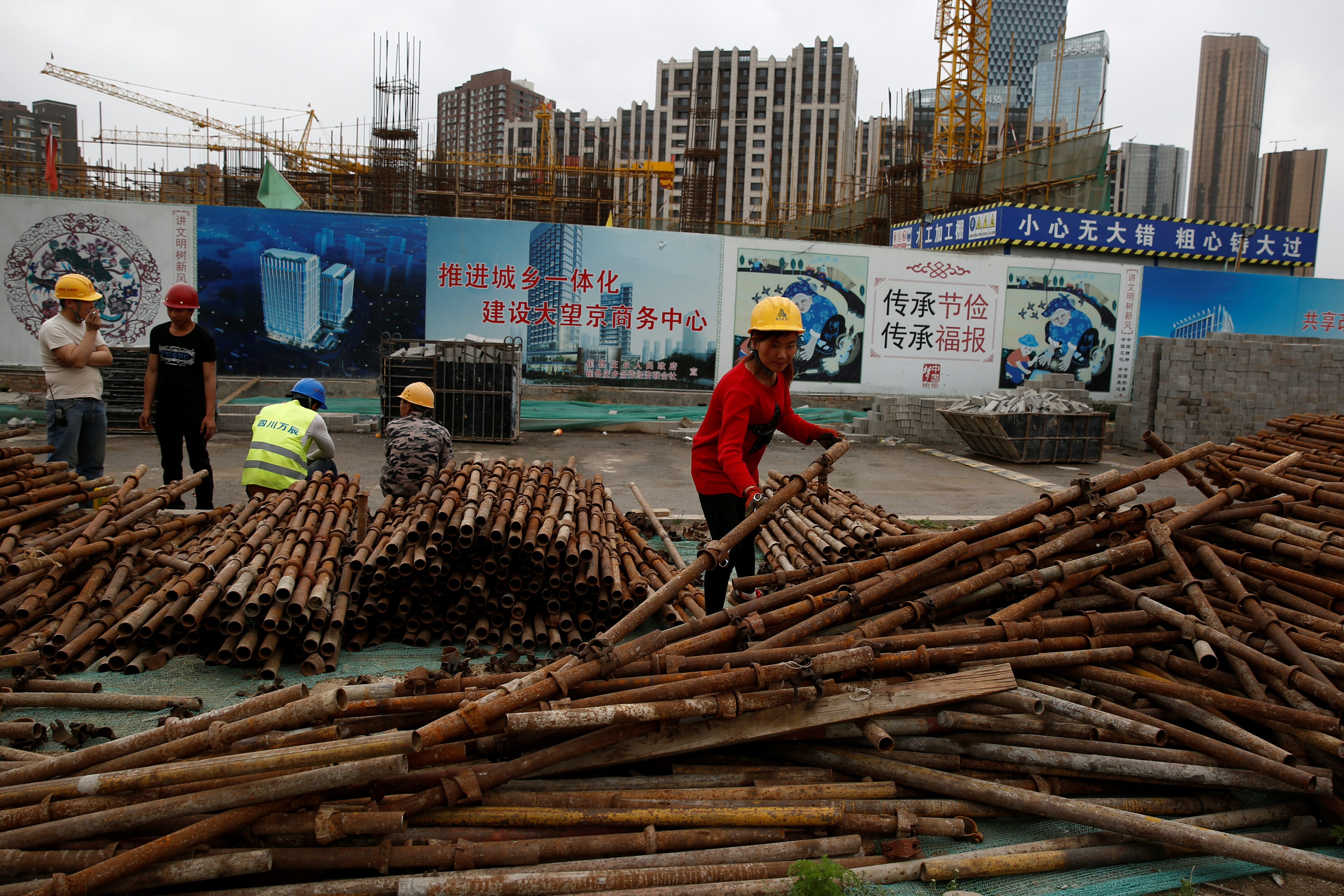 A woman sorts scaffolding poles at a construction site near recently erected office and residential high-rises in Beijing, China April 20, 2017. REUTERS/Thomas Peter - RTS1342V