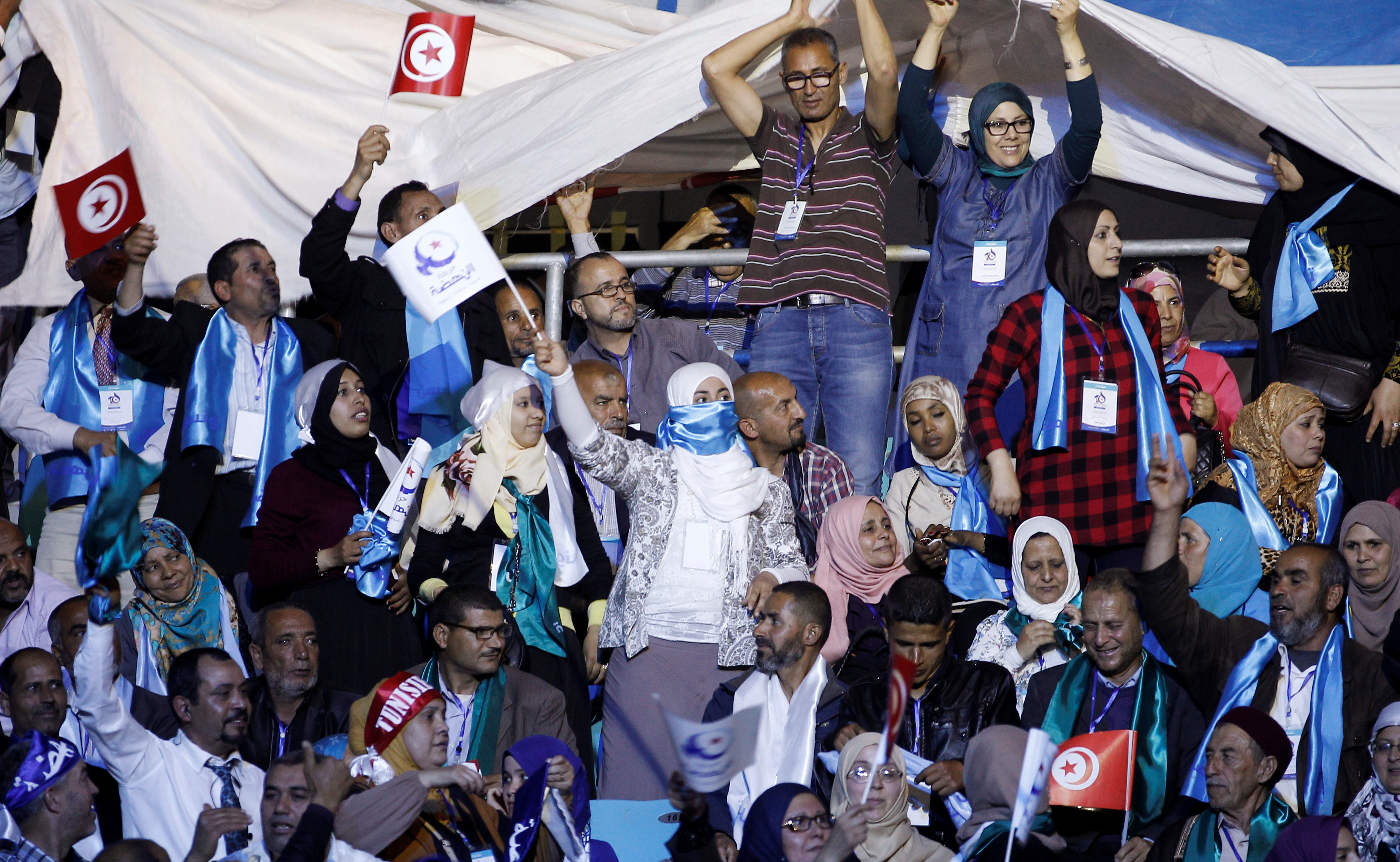 Supporters of the Ennahda movement holds flags during the movement's congress in Tunis,Tunisia May 20, 2016. REUTERS/Zoubeir Souissi - RTSF8BF