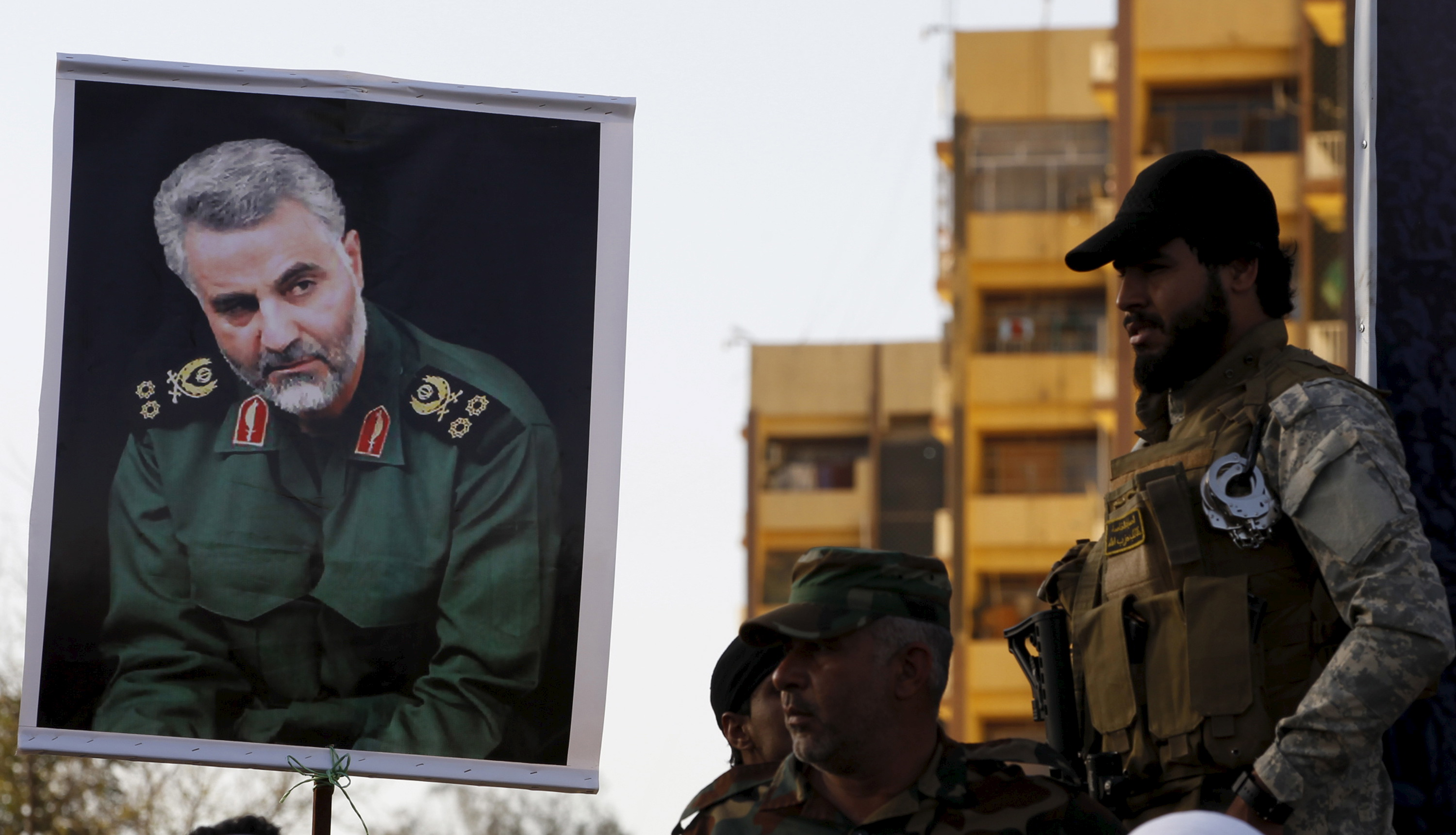 Members from Hashid Shaabi hold a portrait of Quds Force Commander Major General Qassem Suleimani during a demonstration in Baghdad to show support for Yemen's Shi'ite Houthis and in protest of the Saudi-led air campaign in Yemen .