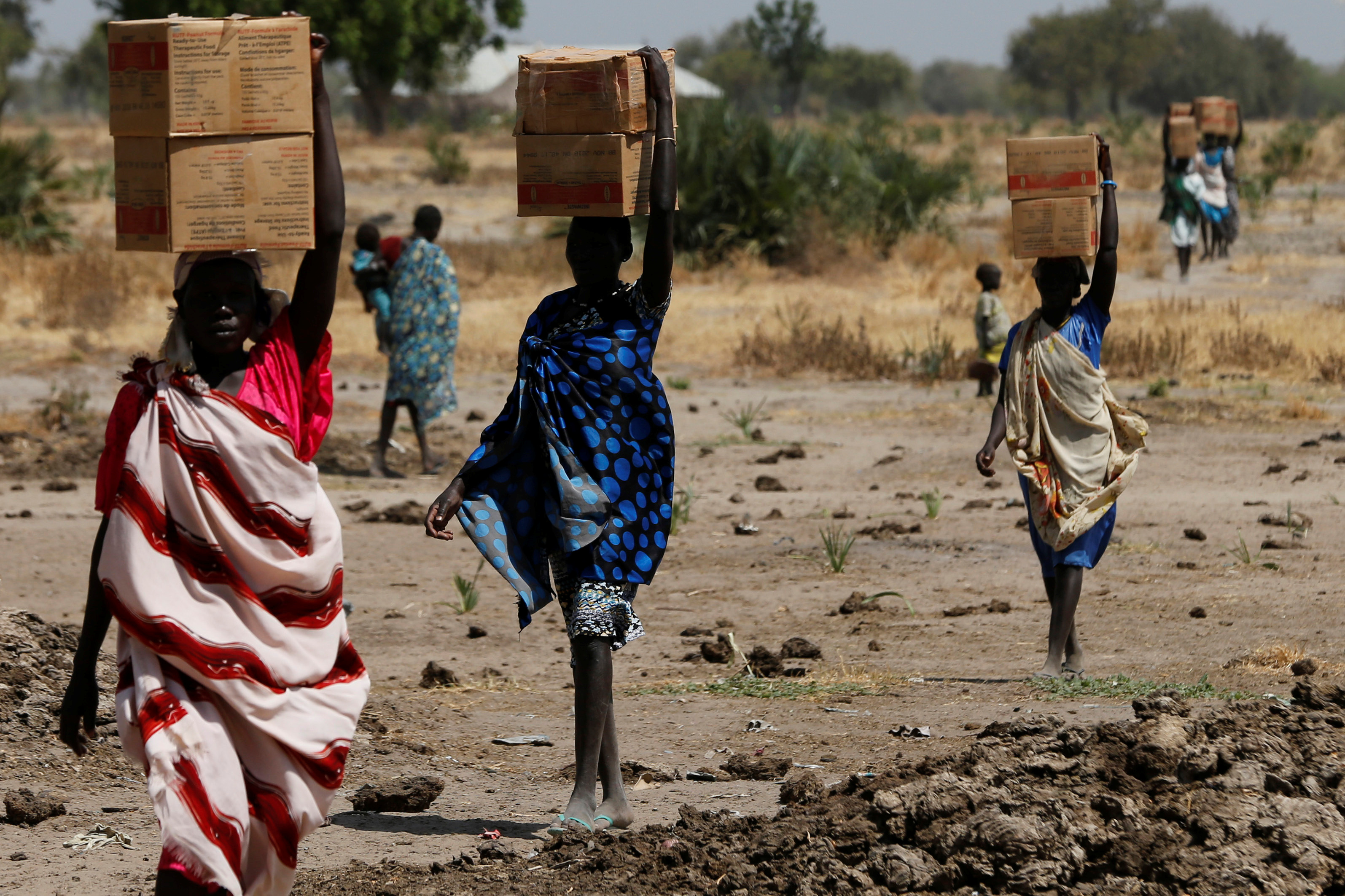 Women carry boxes of nutritional food delivered by the United Nations World Food Programme (UN WFP), in Rubkuai village, Unity State, South Sudan February 16, 2017. Picture taken February 16, 2017. REUTERS/Siegfried Modola - RTSZN6A