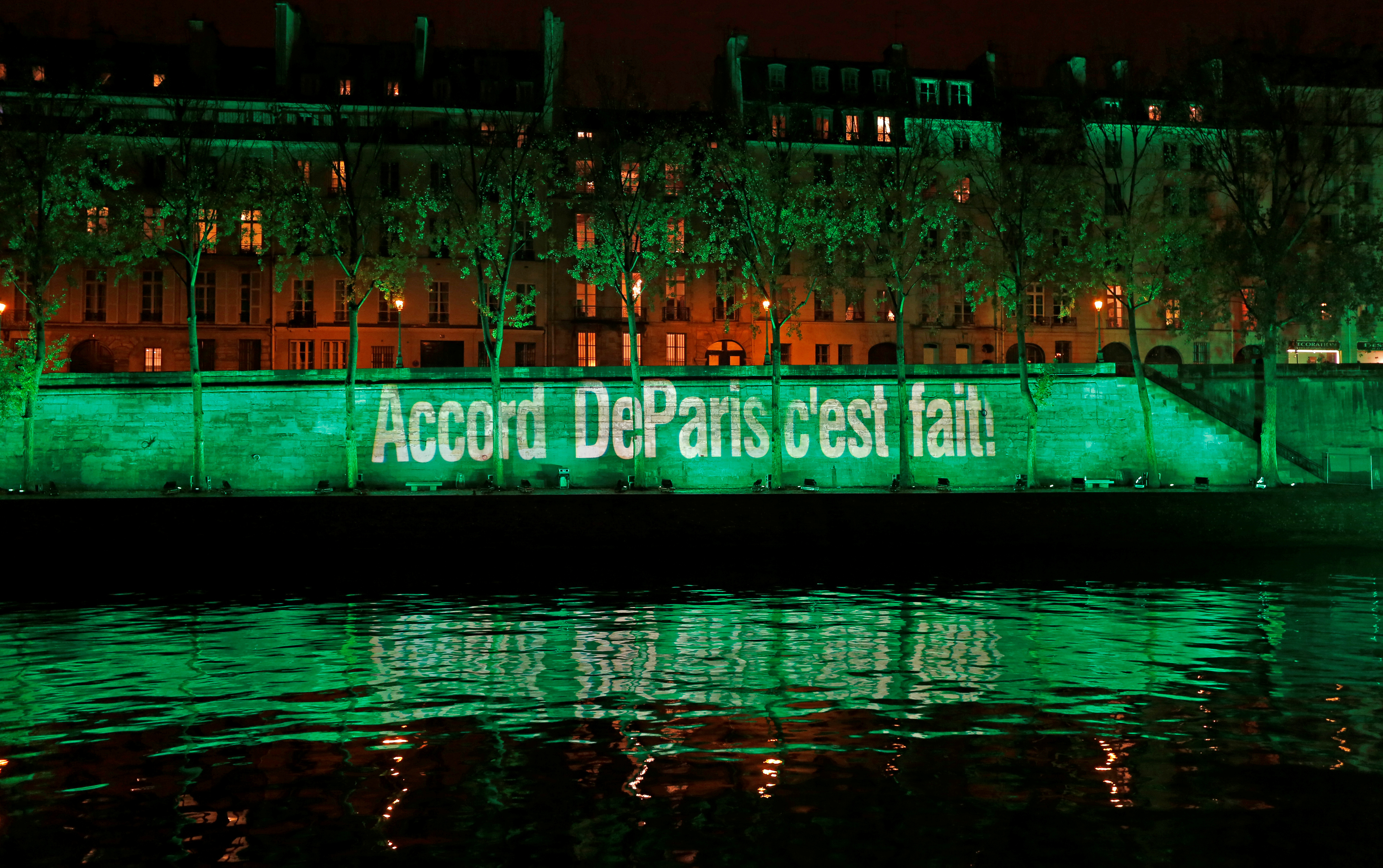"""The banks of the Seine river is illuminated in green with the words """"Paris Agreement is Done"""", to celebrate the Paris U.N. COP21 Climate Change agreement in Paris"""