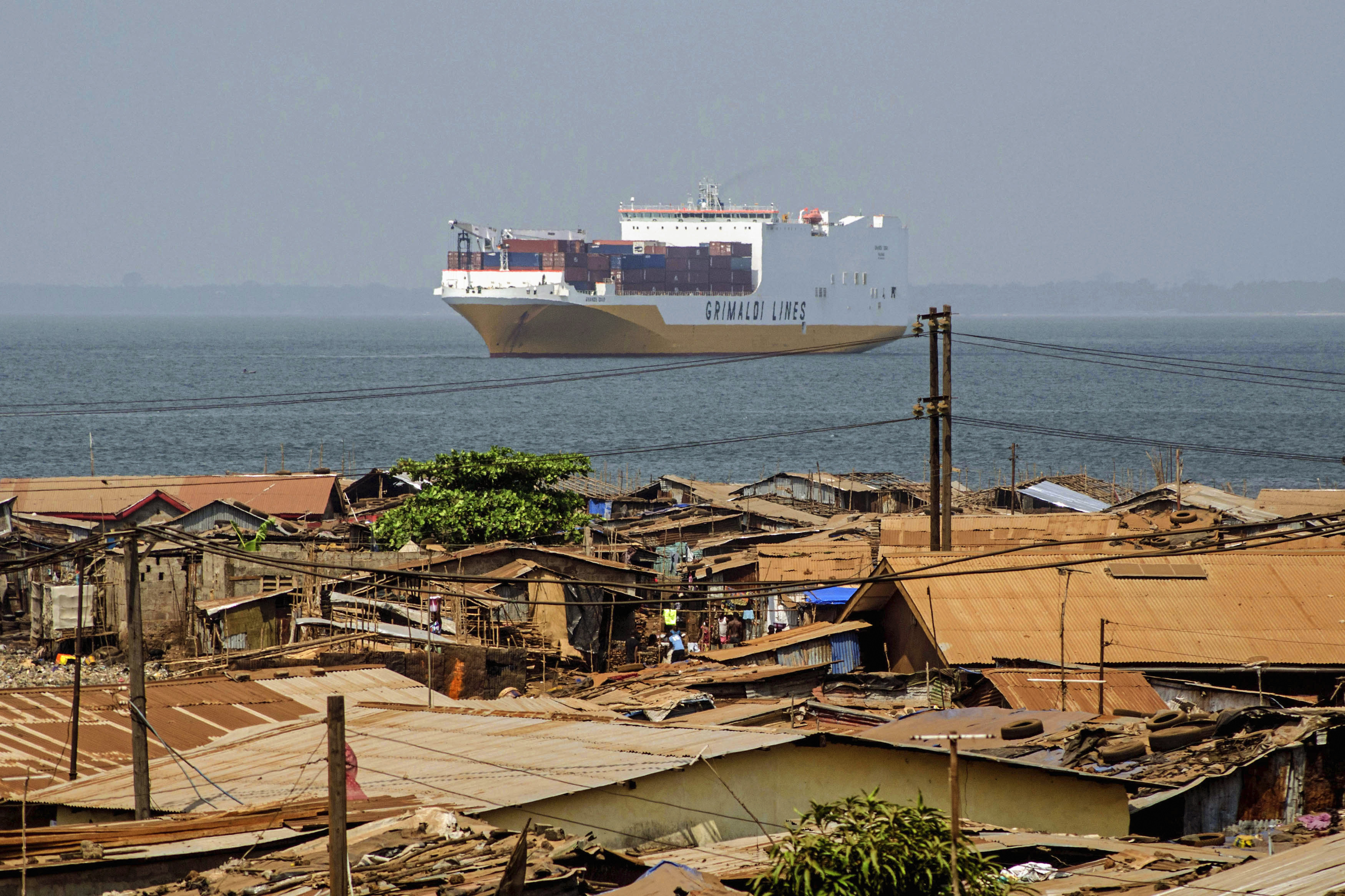 A cargo ship crosses behind Kroo Bay slum in Freetown, January 23, 2014. As evening falls over Sierra Leone's Banana Island archipelago, bats stream from their beachside roosts to circle in their thousands over the jungle village of Dublin. Below them a struggle is playing out over an unexpected commodity - the lowly sea cucumber, a fleshy, sausage-shaped creature that scavenges for food on the seabed. While the Banana Islanders have no use for sea cucumbers, in China they are prized for their medicinal properties and as a natural aphrodisiac. Picture taken January 23, 2014. To match Feature LEONE-SEACUCUMBERS/     REUTERS/Tommy Trenchard (SIERRA LEONE - Tags: ANIMALS BUSINESS FOOD SOCIETY POLITICS MARITIME) - RTR3NHJC